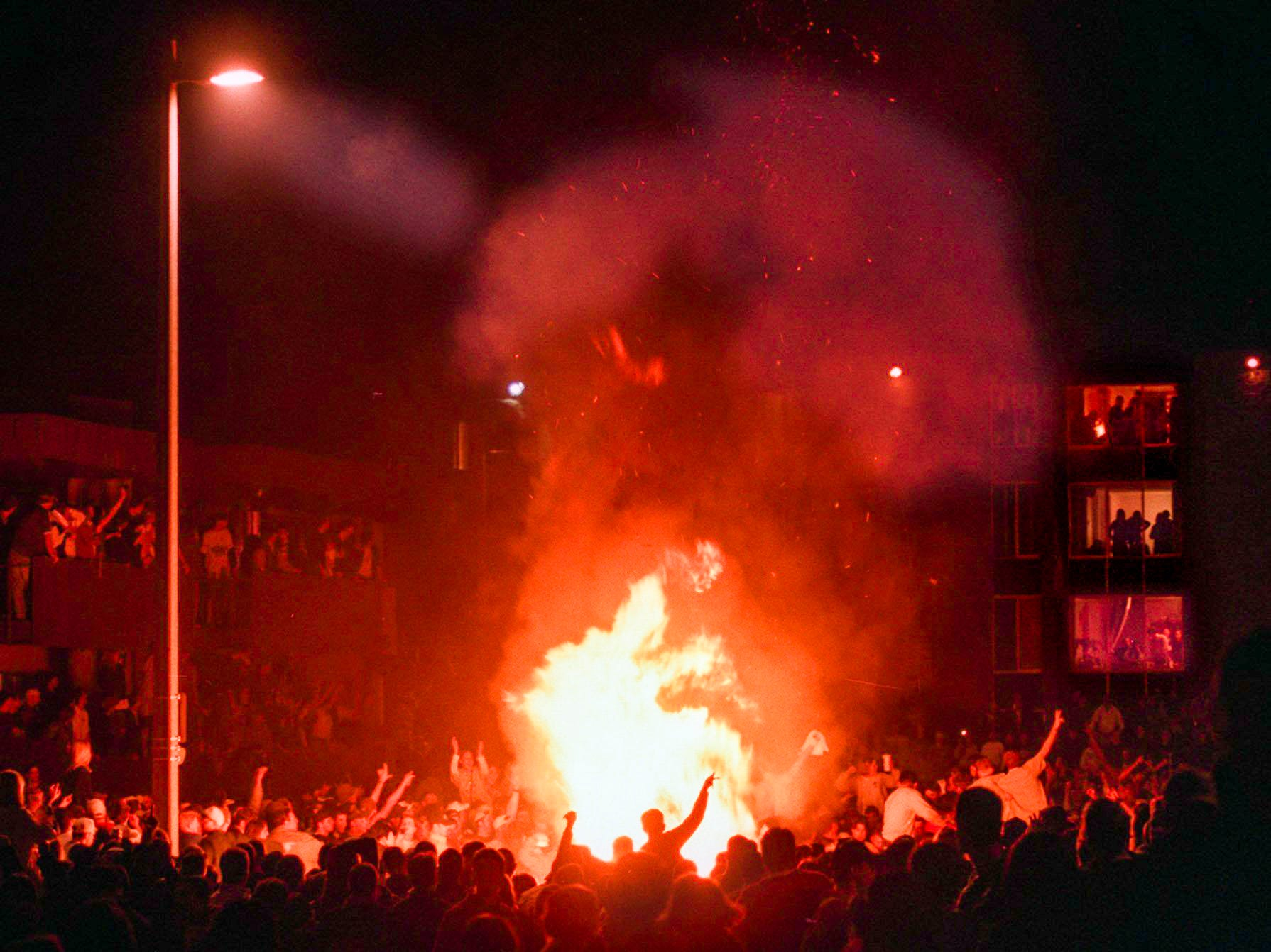 Participants circle a fire in Cedar Village after Michigan State University lost to Duke in the Final Four of the NCAA Men's Basketball Tournament on Saturday, March 27, 1999, in East Lansing.