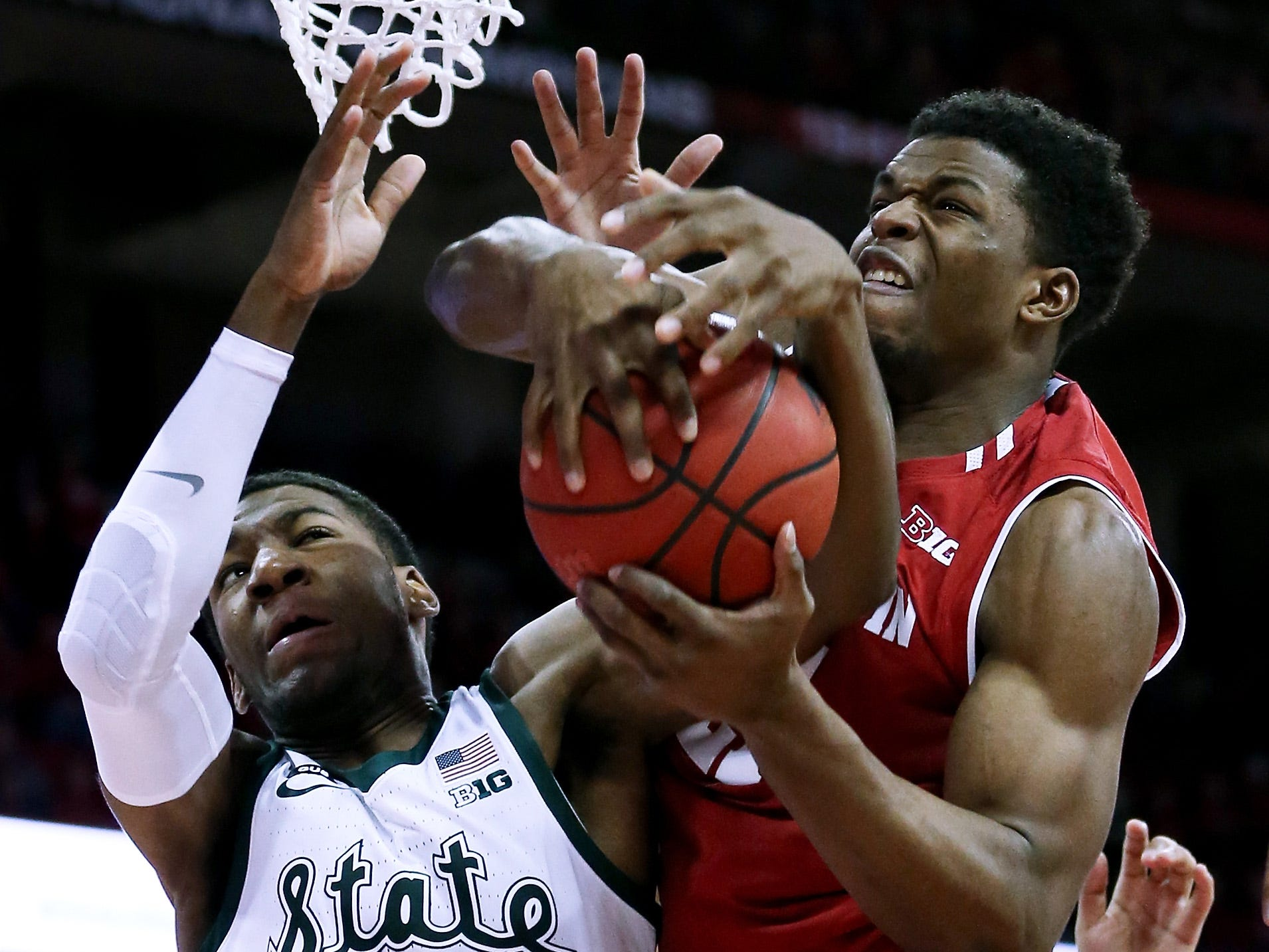Aaron Henry #11 of the Michigan State Spartans and Khalil Iverson #21 of the Wisconsin Badgers battle for a rebound in the first half at the Kohl Center on February 12, 2019 in Madison, Wisconsin.