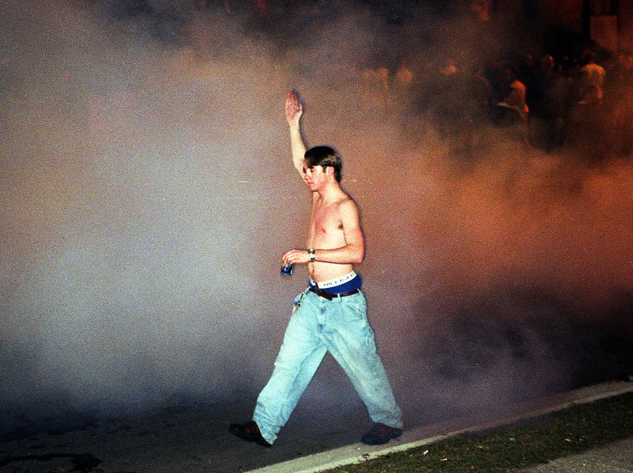 A young man walks through a wall of tear gas at Cedar Village on Saturday, March 27, 1999, in East Lansing.