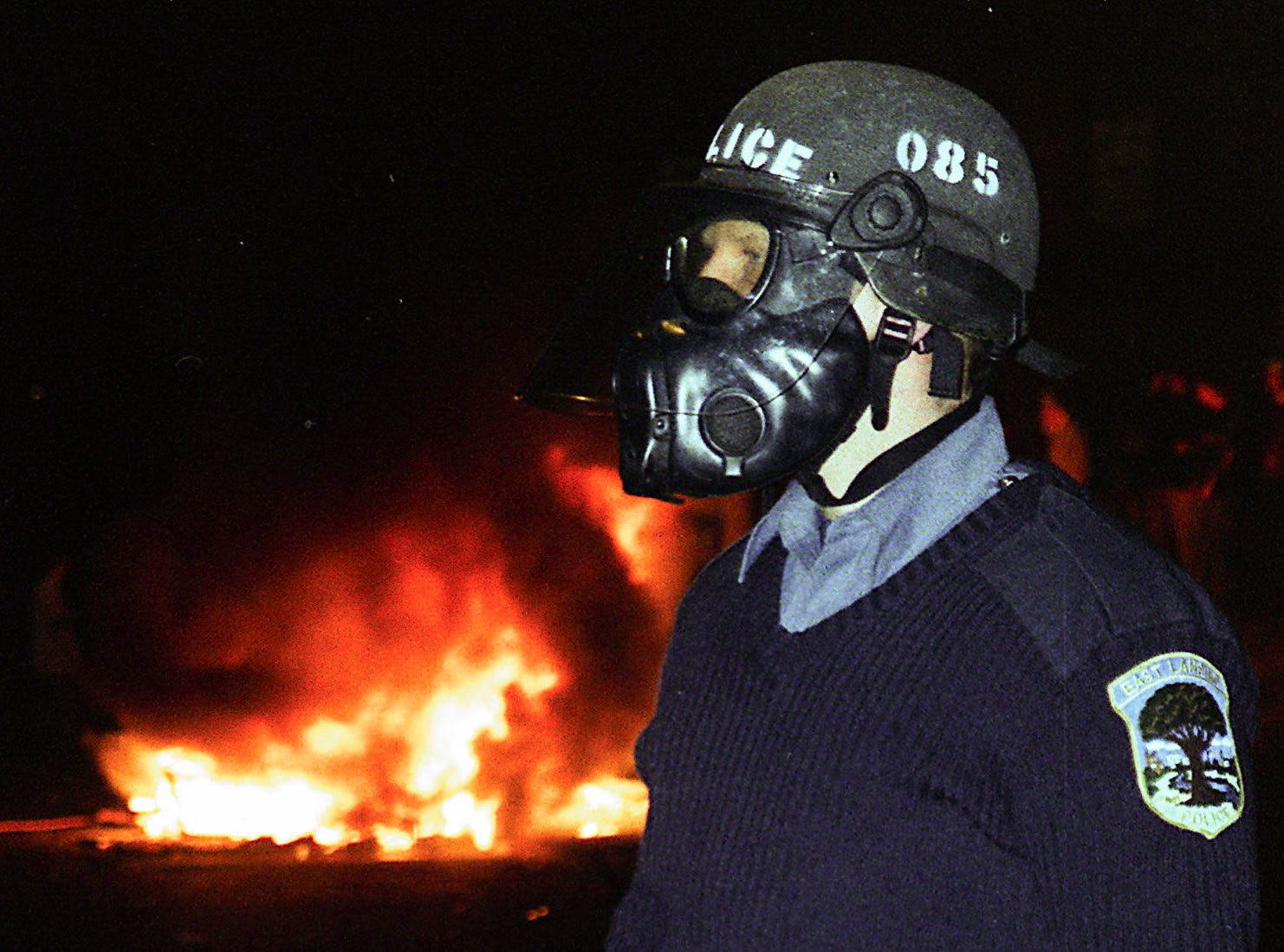 A police officer in a gas mask stands near Grand River Avenue to keep onlookers away from the fires burning in Cedar Village on Saturday, March 27, 1999, in East Lansing.