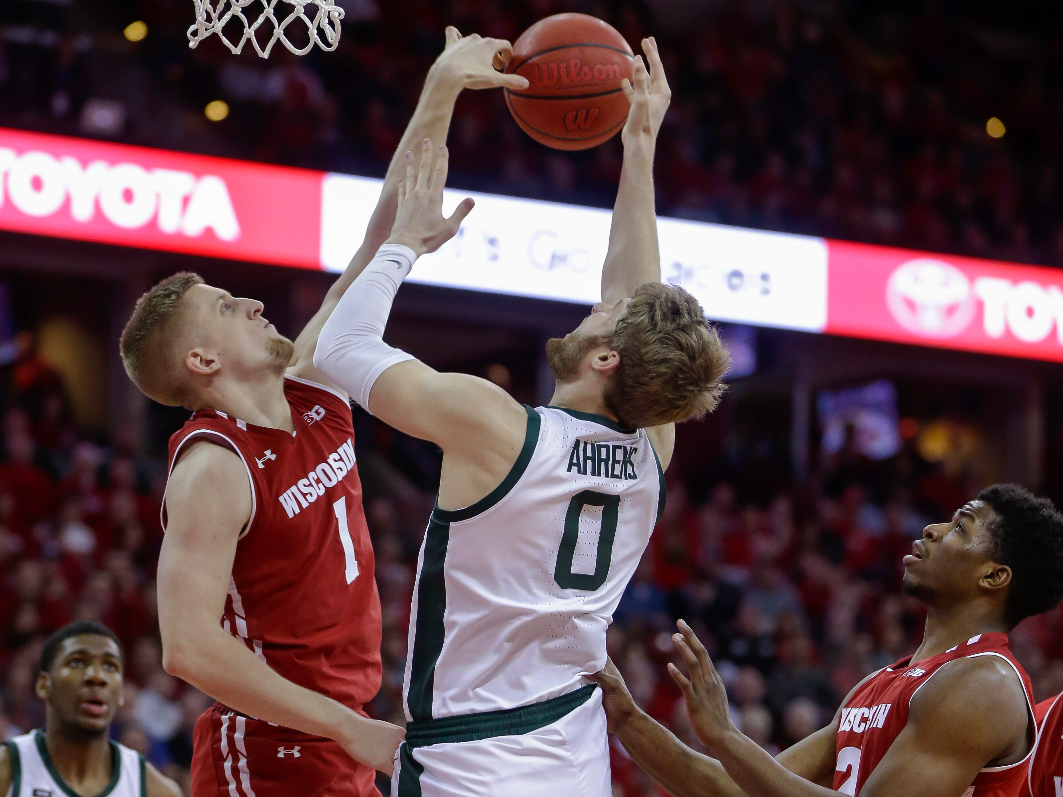 Wisconsin's Brevin Pritzl (1) blocks a shot by Michigan States's Kyle Ahrens (0) during the first half of an NCAA college basketball game Tuesday, Feb. 12, 2019, in Madison, Wis.