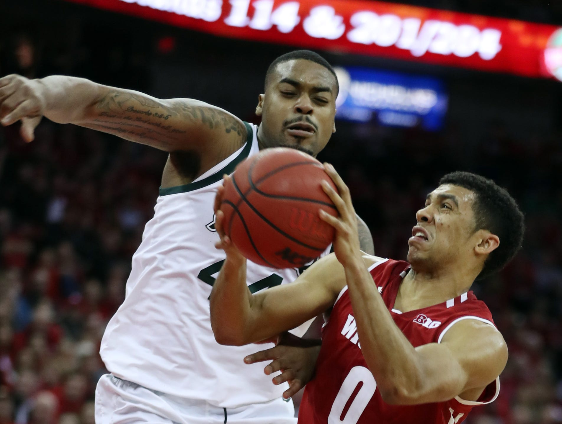 Wisconsin Badgers guard D'Mitrik Trice (0) shoots the ball as Michigan State Spartans forward Nick Ward (44) defends during the second half during the second half at the Kohl Center.