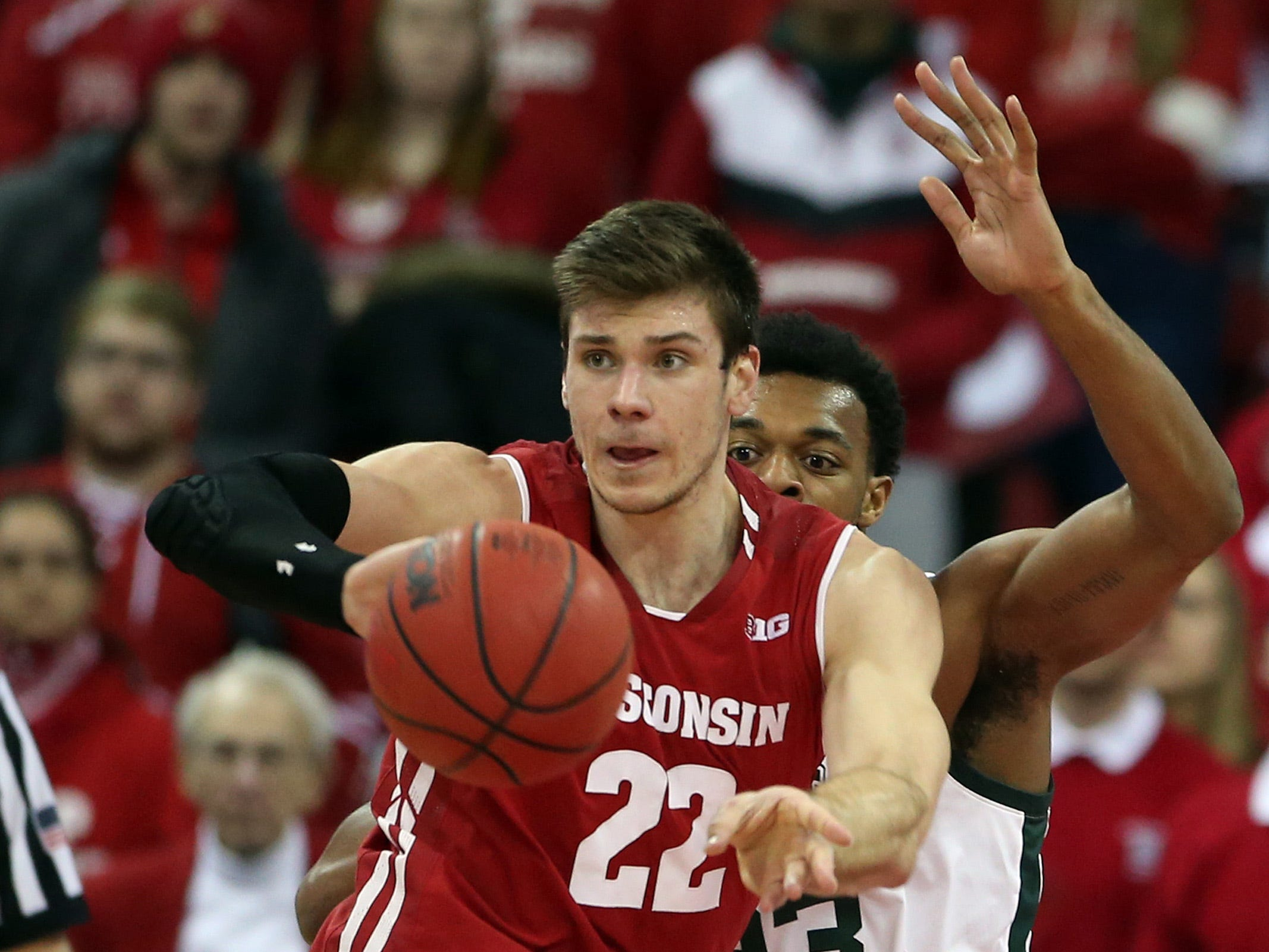 Wisconsin Badgers forward Ethan Happ (22) passes the ball as Michigan State Spartans forward Xavier Tillman (23) defends during the first half at the Kohl Center.