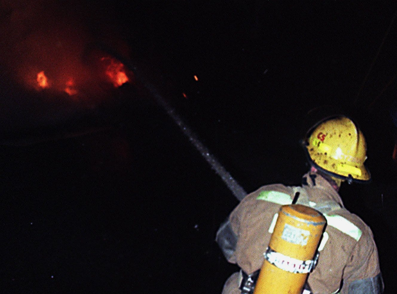 An East Lansing fire fighter puts out one of the many fires set throughout Cedar Village on Saturday, March 27, 1999, in East Lansing.
