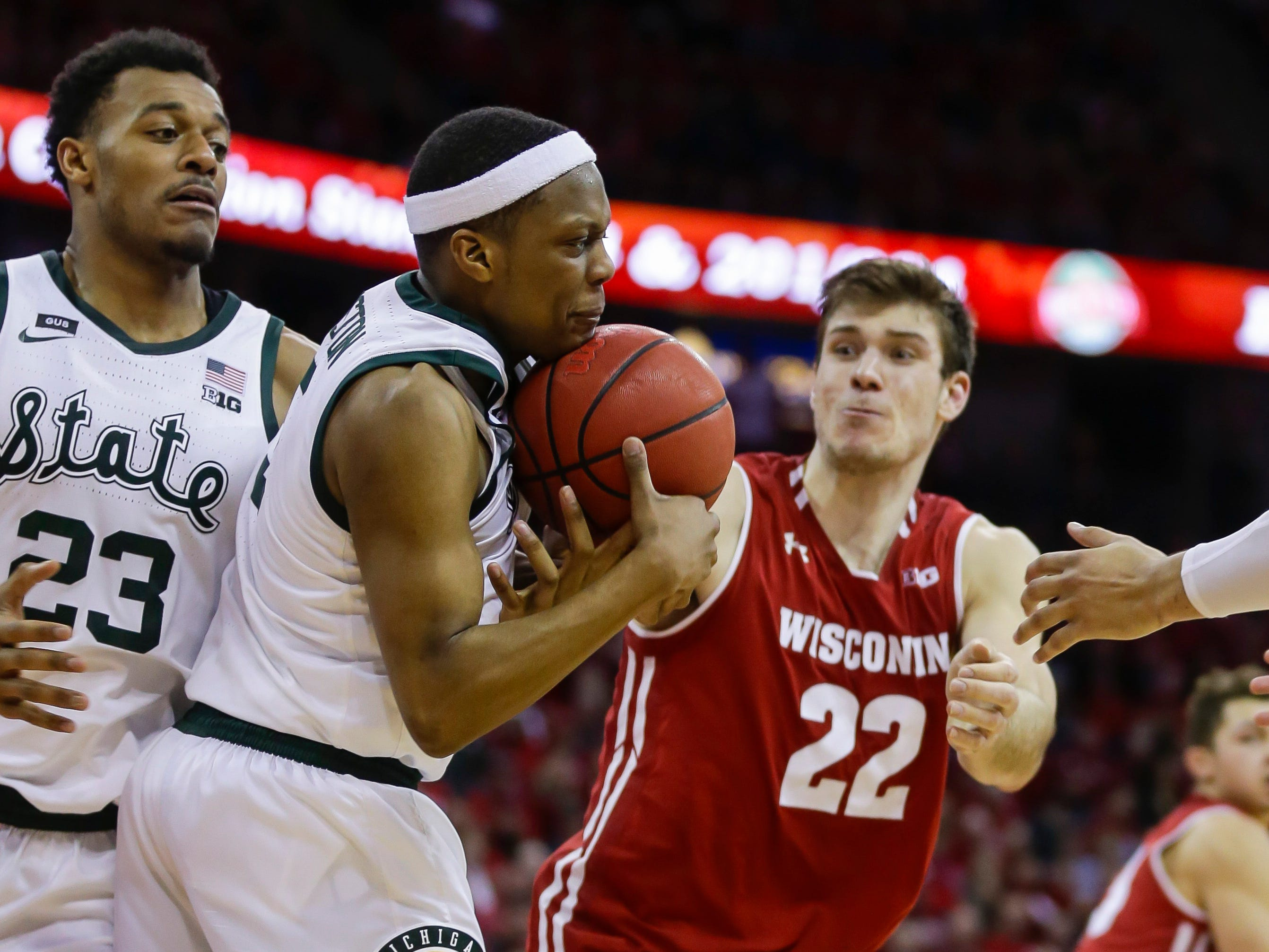 Michigan States's Cassius Winston (5) grabs a defensive rebound next to Wisconsin's Ethan Happ (22) during the second half of an NCAA college basketball game Tuesday, Feb. 12, 2019, in Madison, Wis. Michigan State won 67-59.