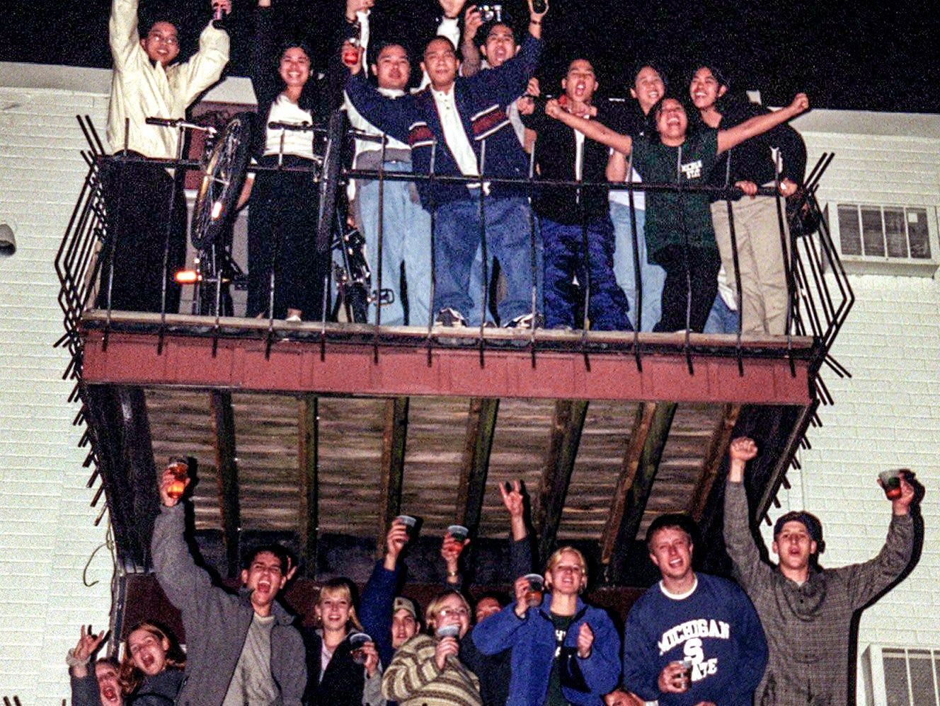 Cedar Village residents celebrate at half-time of the Final Four game between Michigan State University and Duke in the NCAA Men's Basketball Tournament  on Saturday, March 27, 1999, in East Lansing. MSU lost the game, triggering bonfires and riots in the city.