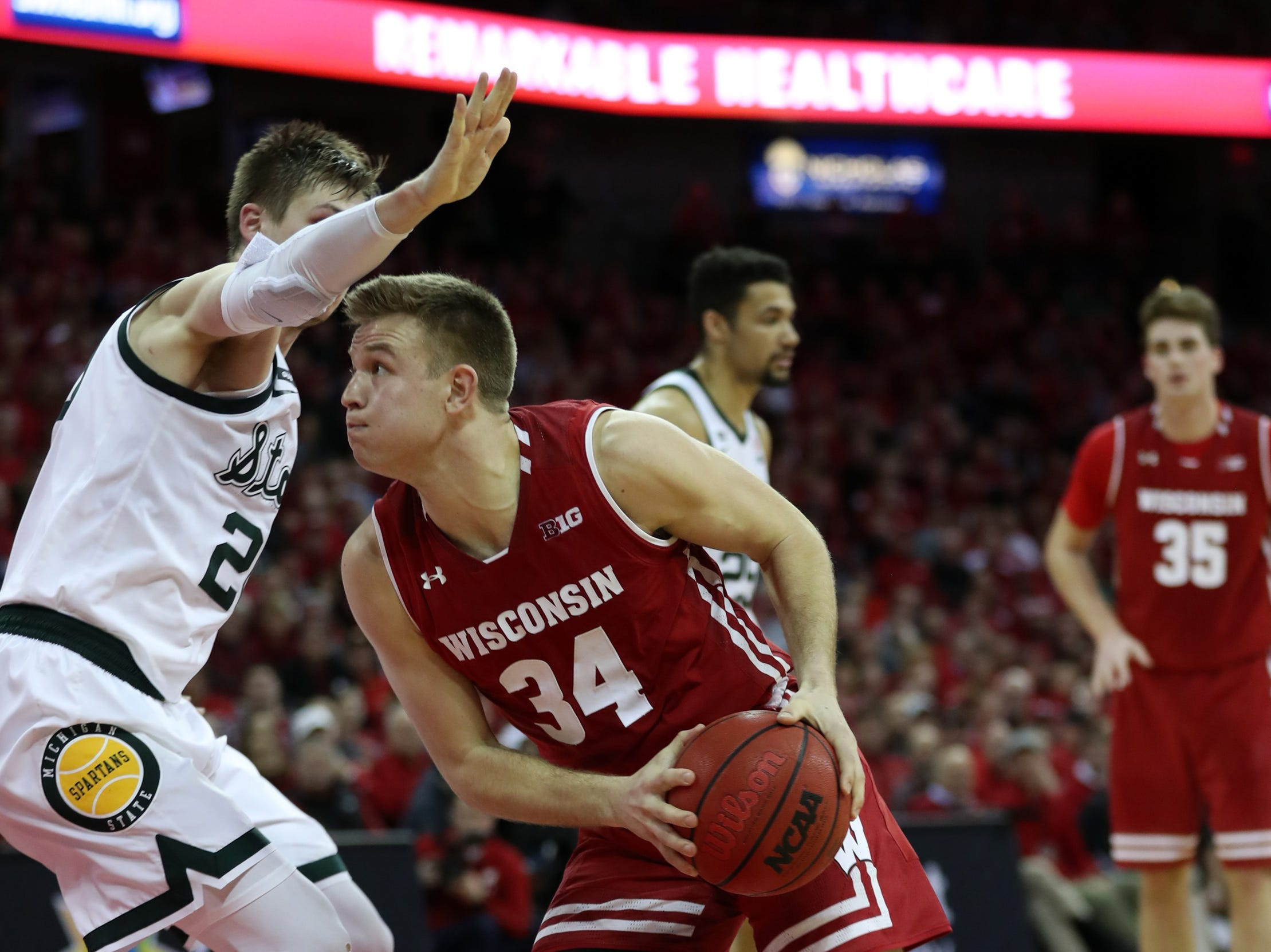 Wisconsin Badgers guard Brad Davison (34) controls the ball as Michigan State Spartans guard Matt McQuaid (left) defends during the second half at the Kohl Center.