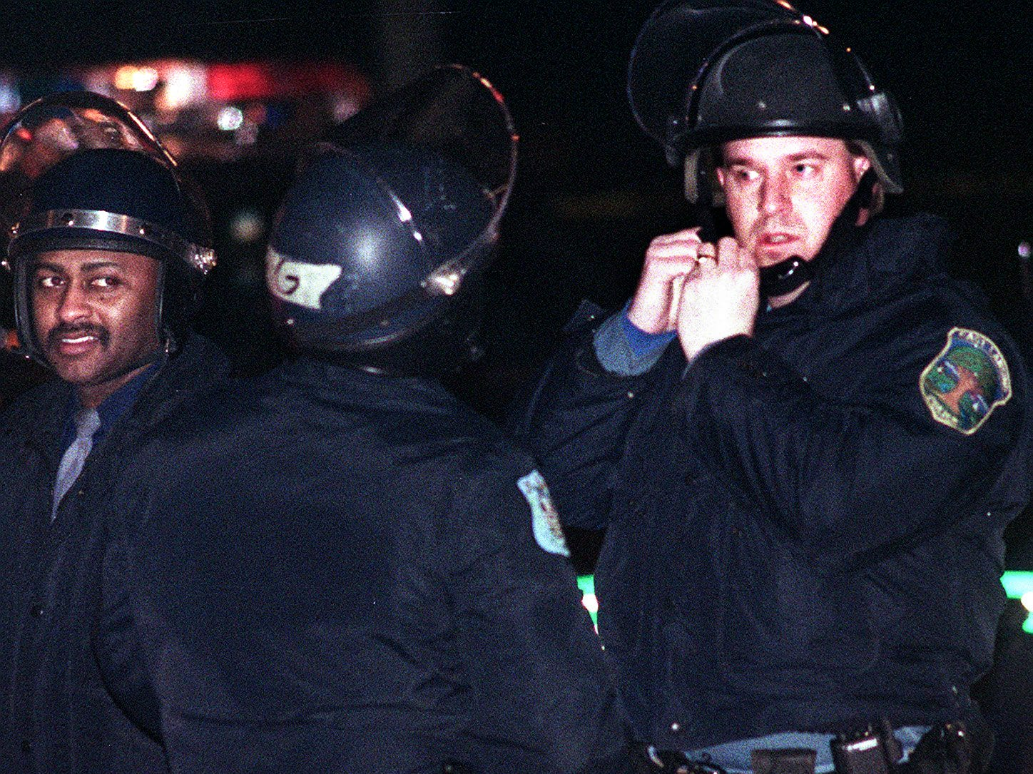 Police suit up in their riot gear as people in the Cedar Village complex set bonfires on Saturday, March 27, 1999, in East Lansing.