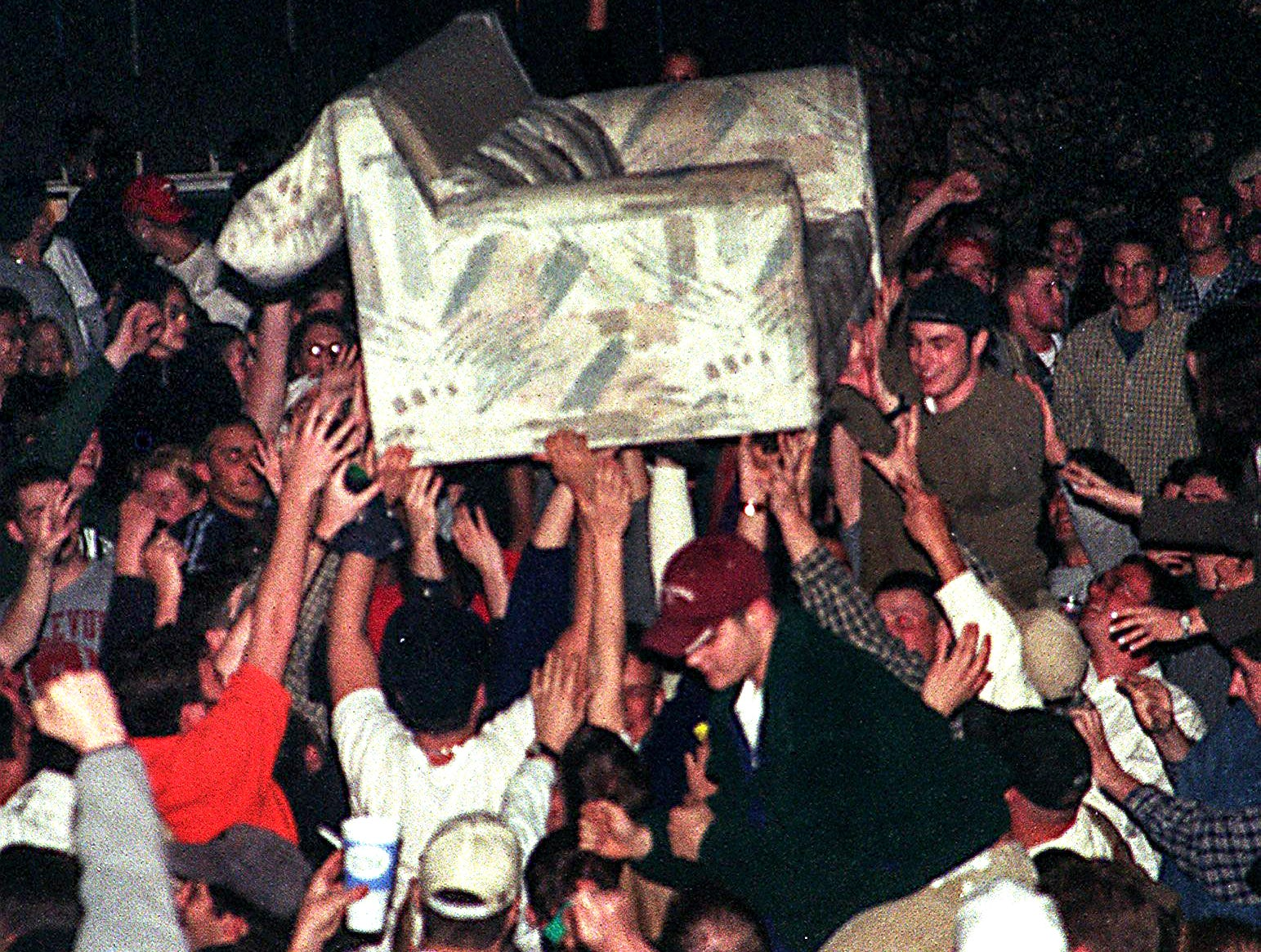 People in Cedar Village pass a couch overhead minutes after the Michigan State game ended in a loss to Duke in the Final Four of the NCAA Men's Basketball Tournament on Saturday, March 27, 1999, in East Lansing. The first of a series of fires started minutes later.