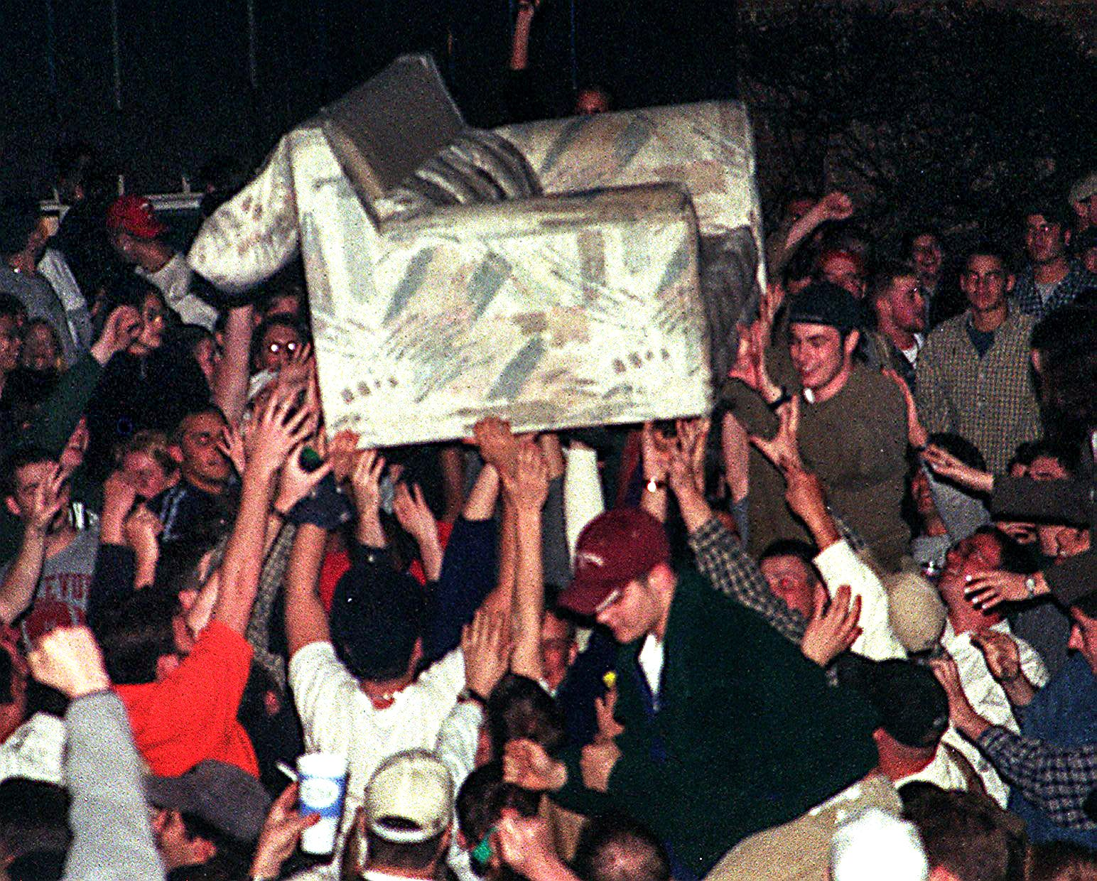 People in Cedar Village pass a cot beyond mins after a Michigan State diversion finished in a detriment to Duke in a Final Four of a NCAA Men's Basketball Tournament on Saturday, Mar 27, 1999, in East Lansing. The initial of a array of fires started mins later.