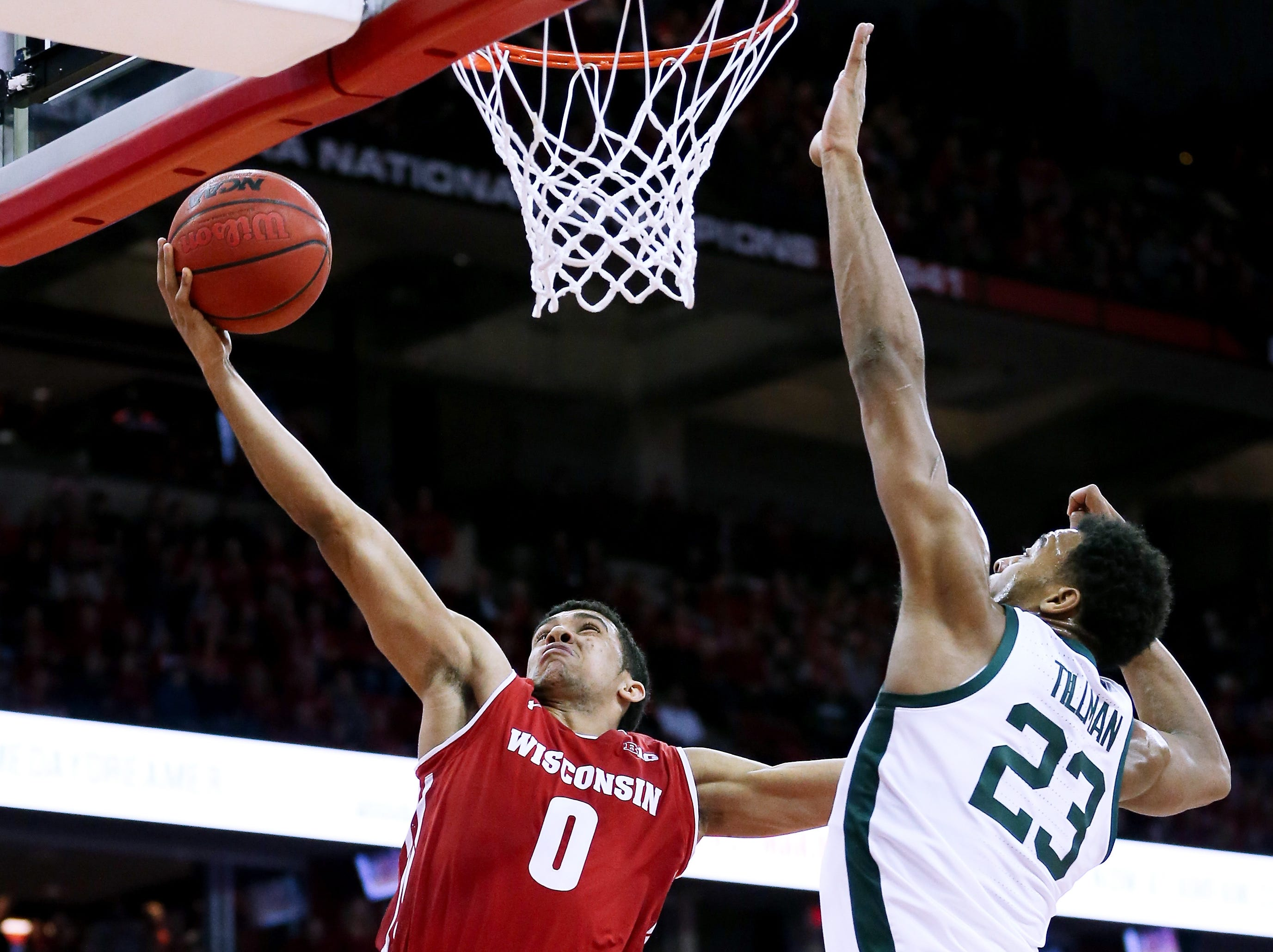 D'Mitrik Trice #0 of the Wisconsin Badgers attempts a shot while being guarded by Xavier Tillman #23 of the Michigan State Spartans in the first half at the Kohl Center on February 12, 2019 in Madison, Wisconsin.
