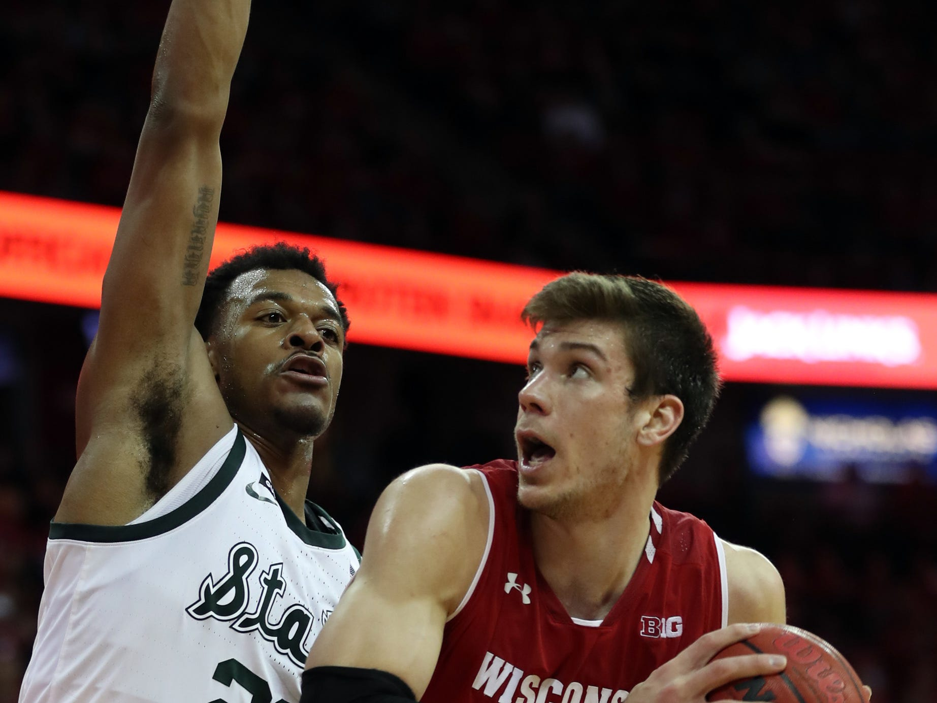 Wisconsin Badgers forward Ethan Happ (22) works the ball as Michigan State Spartans forward Xavier Tillman ((left) defends during the second half at the Kohl Center.