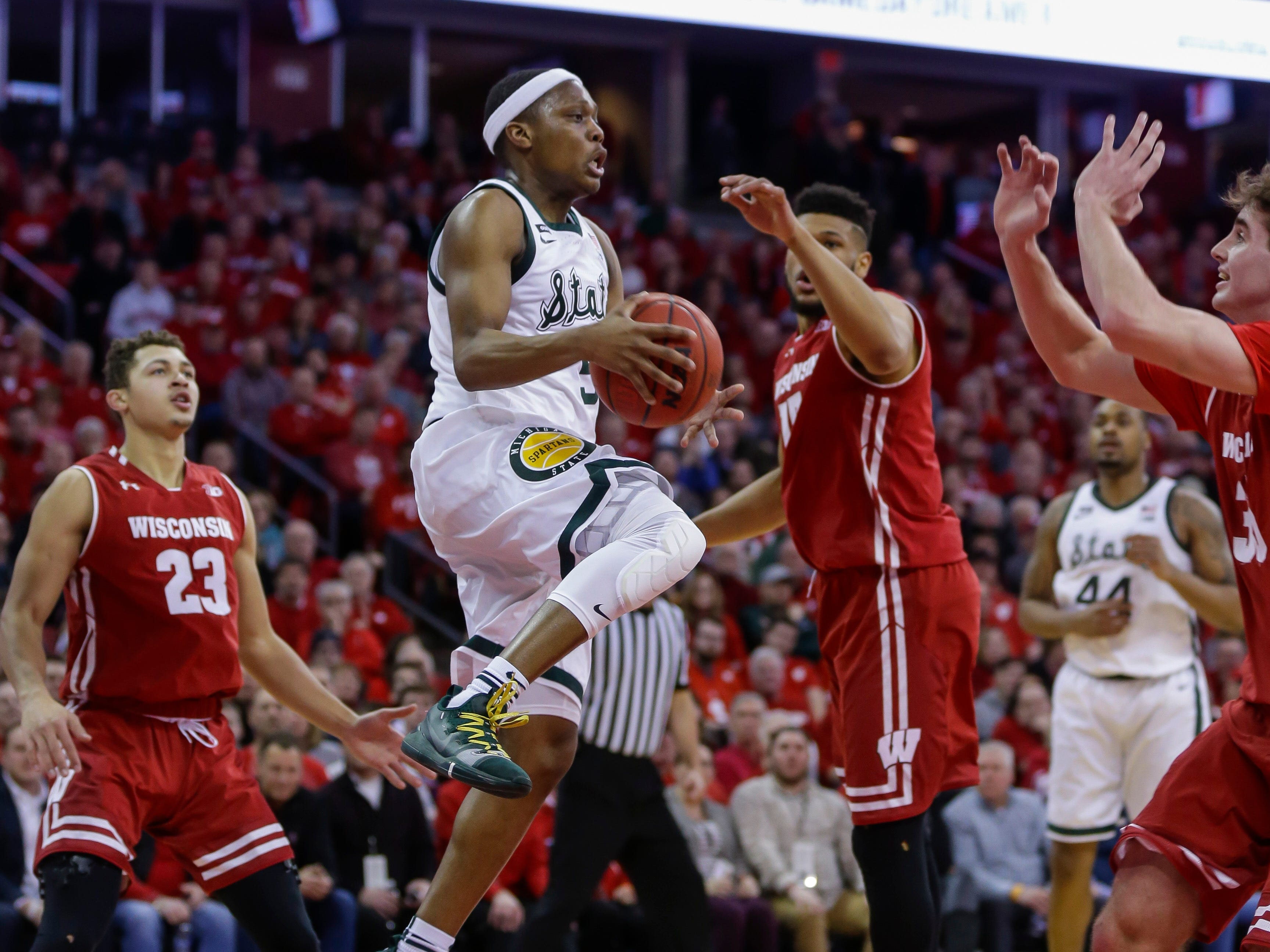 Michigan States's Cassius Winston (5) looks to pass as Wisconsin's Charles Thomas (15) defends during the first half of an NCAA college basketball game Tuesday, Feb. 12, 2019, in Madison, Wis.