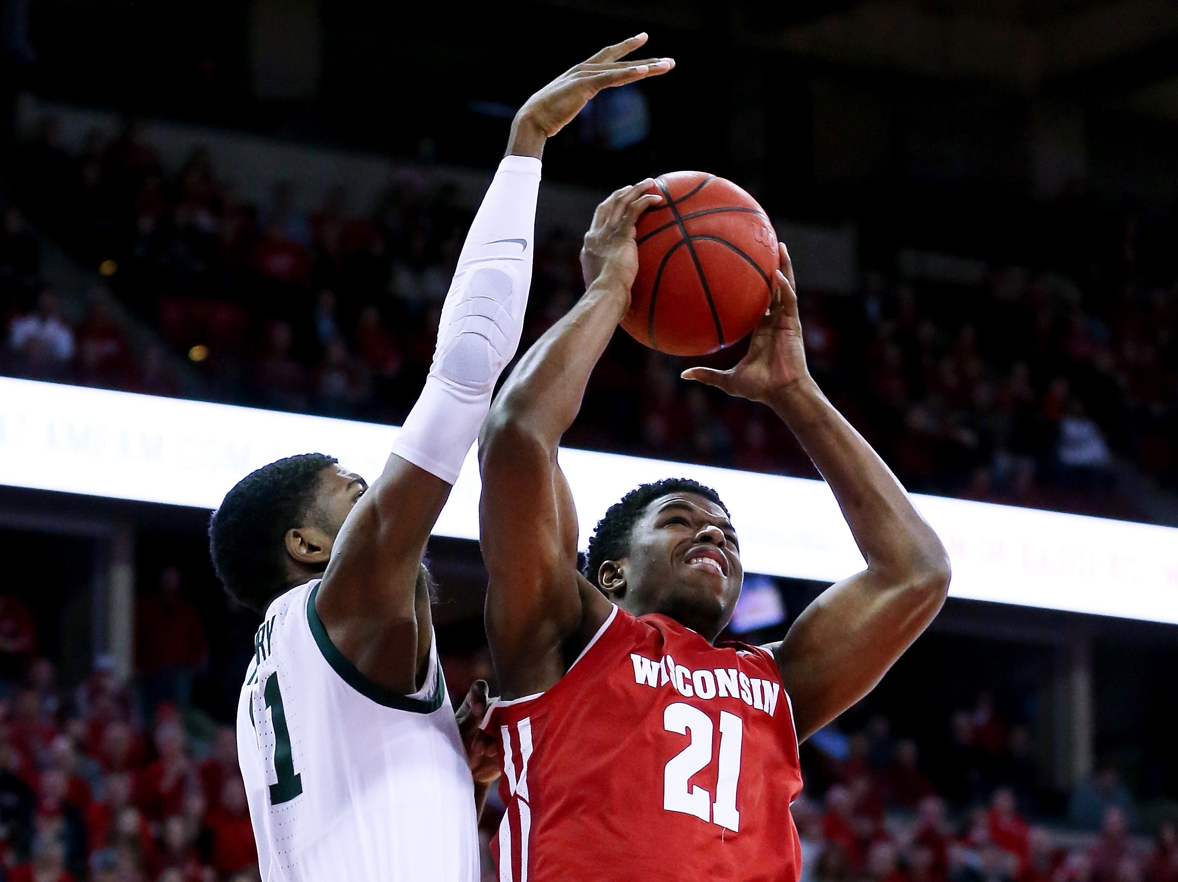 MADISON, WISCONSIN - FEBRUARY 12:  Khalil Iverson #21 of the Wisconsin Badgers attempts a shot while being guarded by Aaron Henry #11 of the Michigan State Spartans in the first half at the Kohl Center on February 12, 2019 in Madison, Wisconsin.