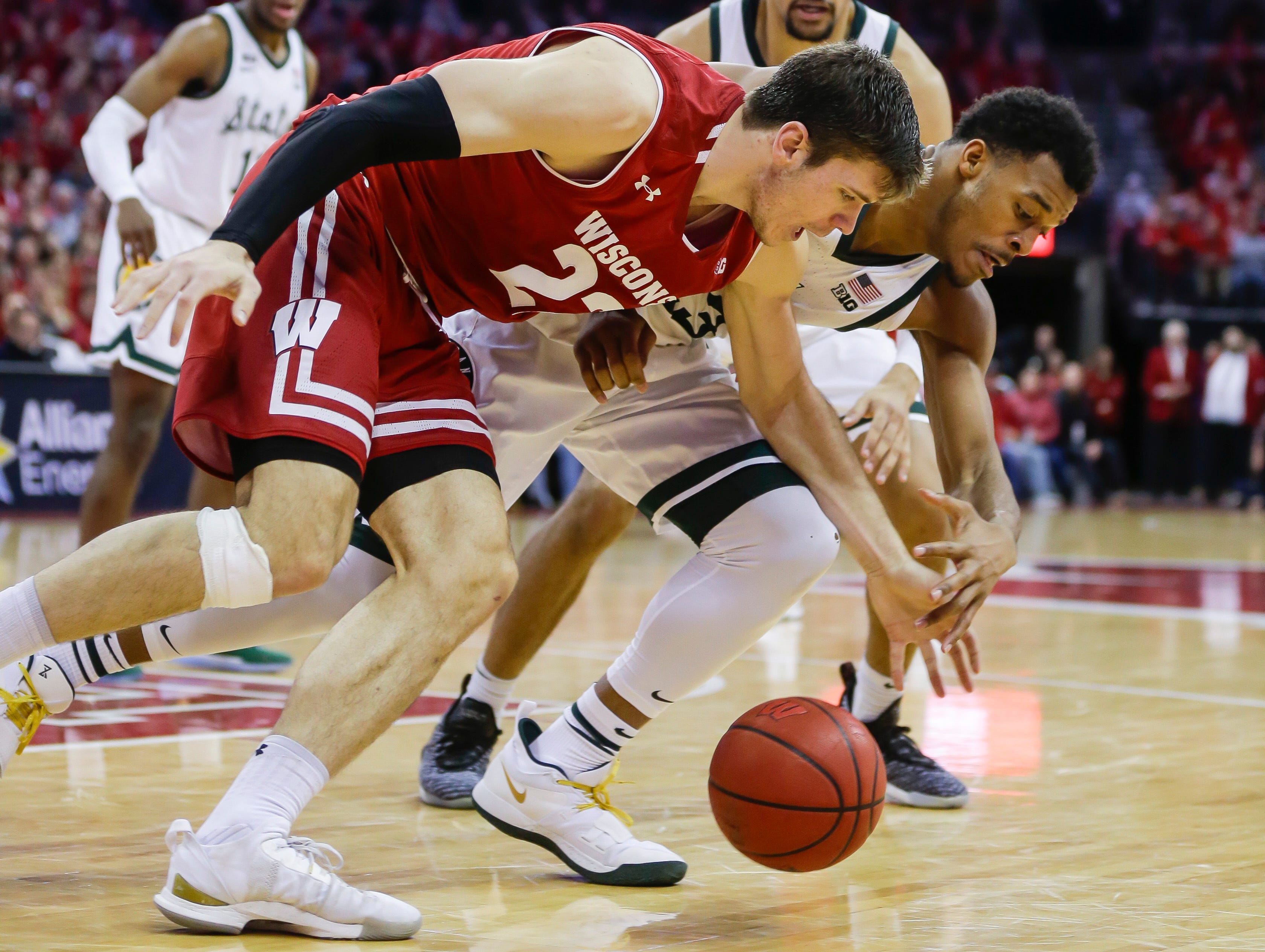 Wisconsin's Ethan Happ (22) and Michigan States's Xavier Tillman go after a loose ball during the second half of an NCAA college basketball game Tuesday, Feb. 12, 2019, in Madison, Wis. Michigan State won 67-59.