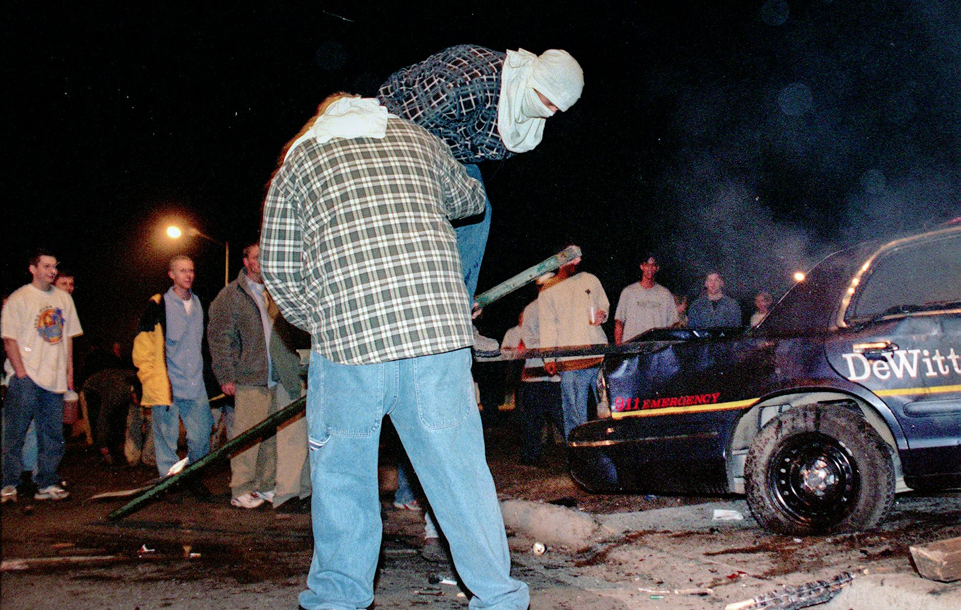 Men try to open a box of a damanged DeWitt Township Police automobile on Saturday, Mar 27, 1999, in East Lansing.