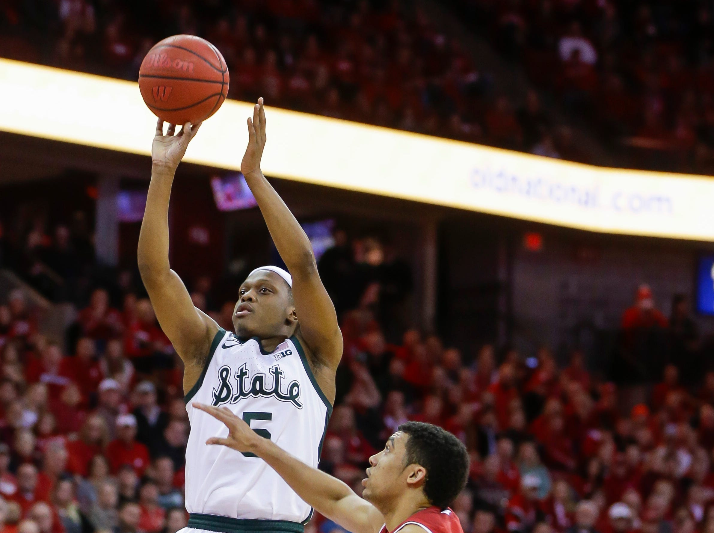 Michigan States's Cassius Winston (5) shoots next to Wisconsin's D'Mitrik Trice (0) during the first half of an NCAA college basketball game Tuesday, Feb. 12, 2019, in Madison, Wis. Michigan State won 67-59.