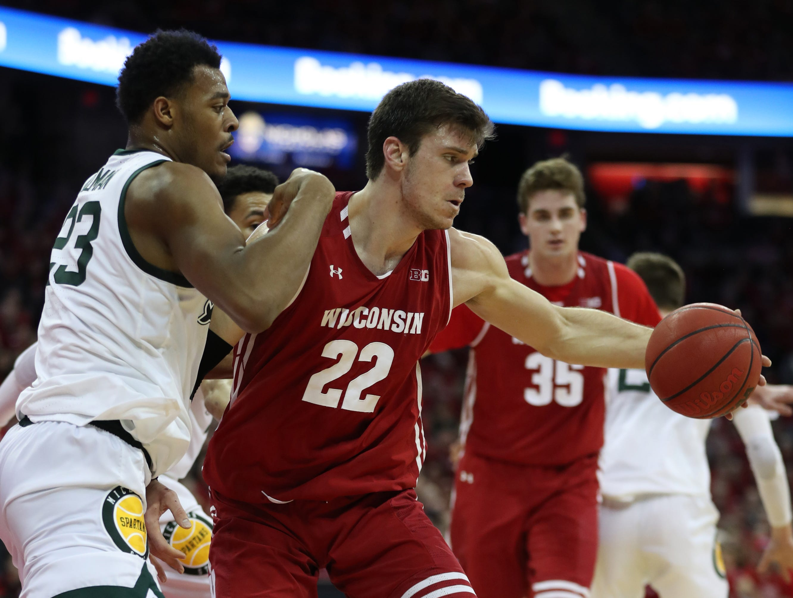 Wisconsin Badgers forward Ethan Happ (22) reaches for the ball as Michigan State Spartans forward Xavier Tillman (23) defends during the second half at the Kohl Center.