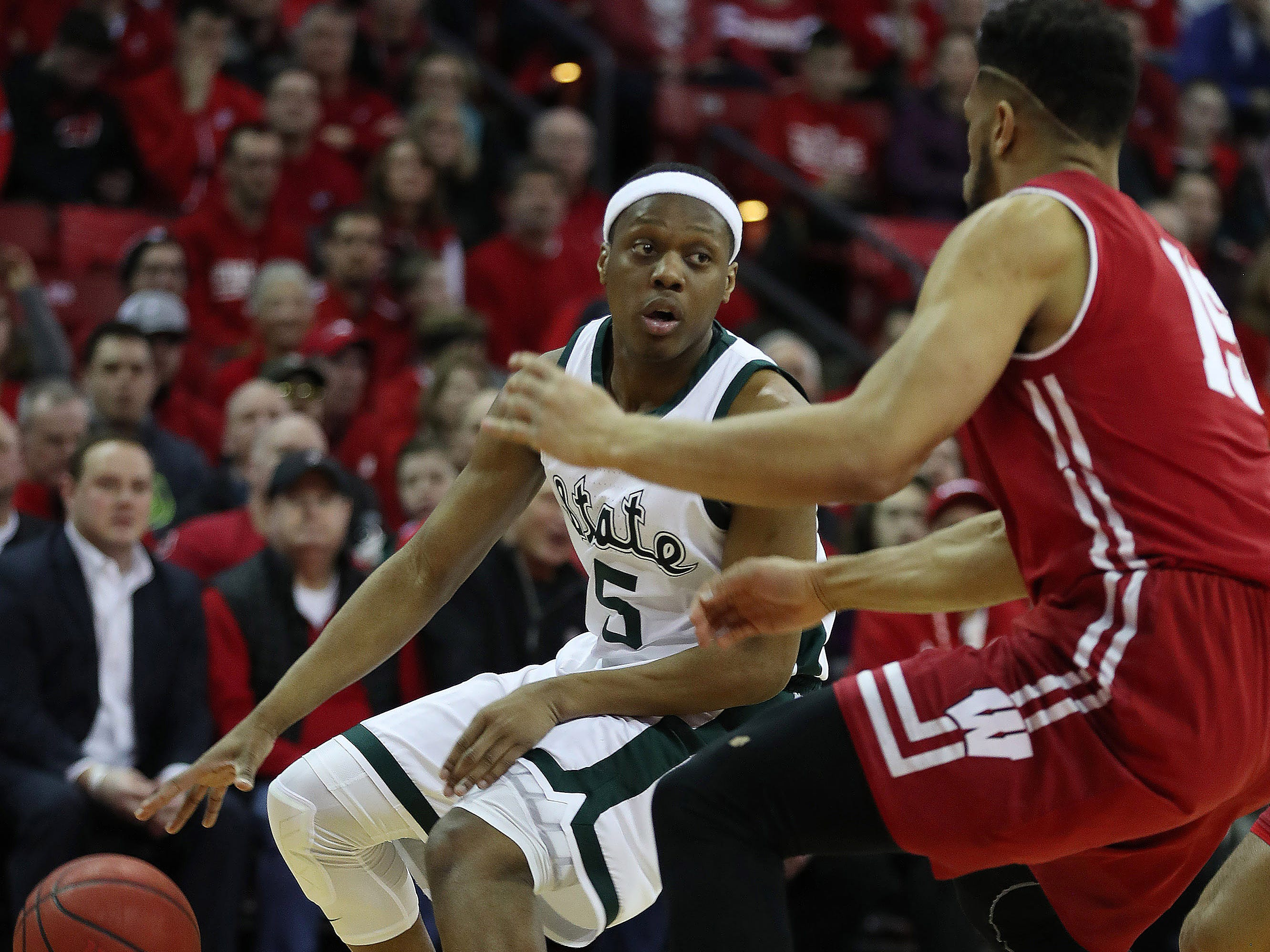 Michigan State Spartans guard Cassius Winston (5) dribbles the ball as Wisconsin Badgers forward Charles Thomas (right) defends during the first half at the Kohl Center.
