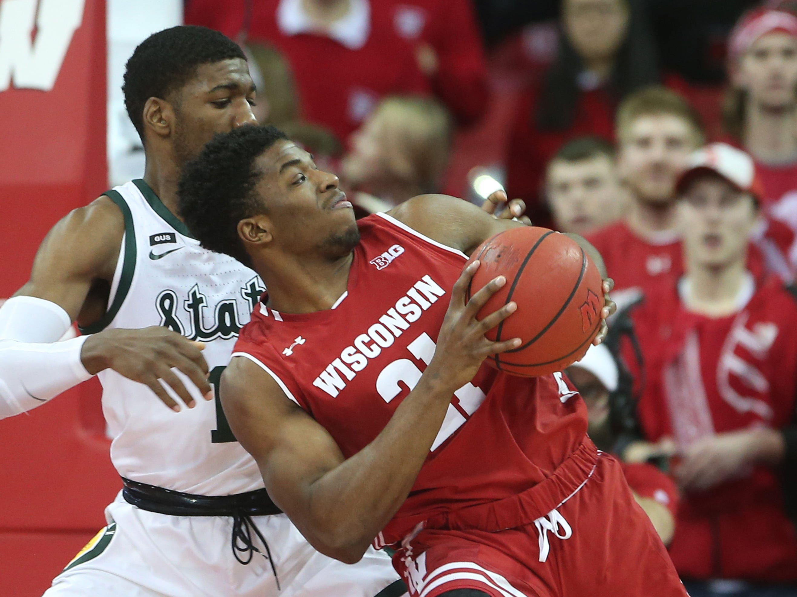 Wisconsin Badgers guard Khalil Iverson (21) controls the ball as Michigan State Spartans forward Aaron Henry (11) defends during the first half at the Kohl Center.