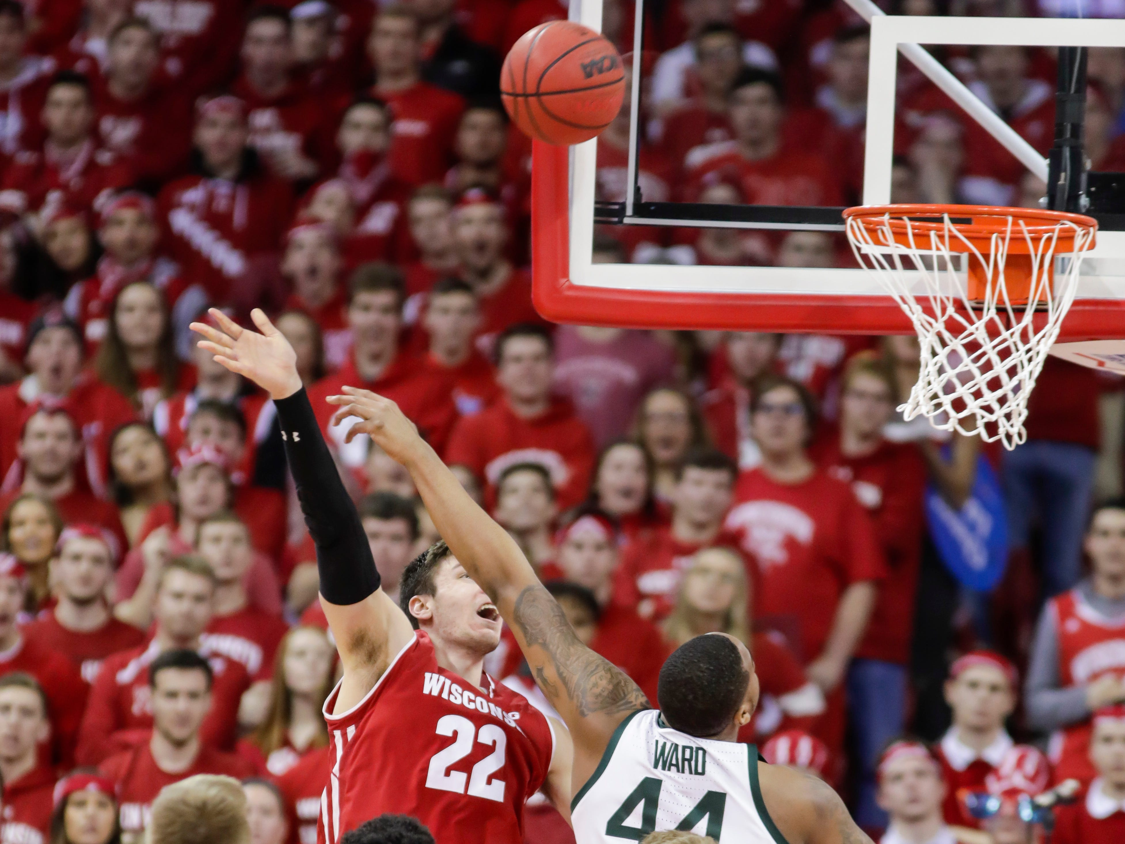 Wisconsin's Ethan Happ (22) and Michigan States's Nick Ward (44) watch Hap's shot during the first half of an NCAA college basketball game Tuesday, Feb. 12, 2019, in Madison, Wis.