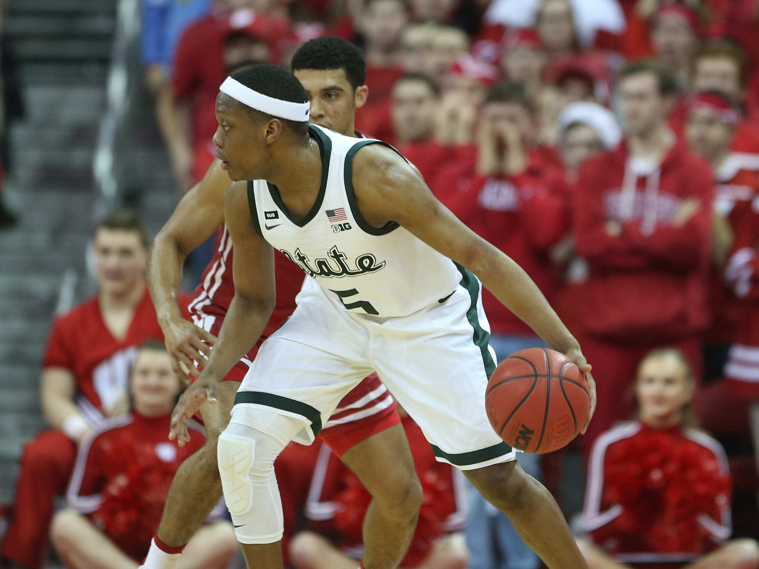 Michigan State Spartans guard Cassius Winston (5) dribbles the ball as Wisconsin Badgers guard D'Mitrik Trice (rear) defends at the Kohl Center.