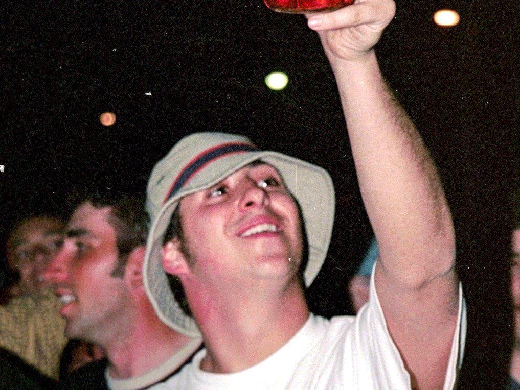 A young man lifts up a bottle of Jim Beam bourbon at Cedar Village on Saturday, March 27, 1999, in East Lansing.