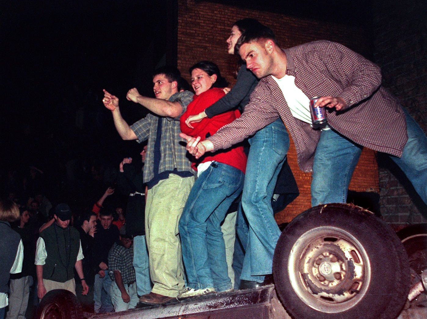 People stand on an overturned car in East Lansing on Saturday, March 27, 1999.