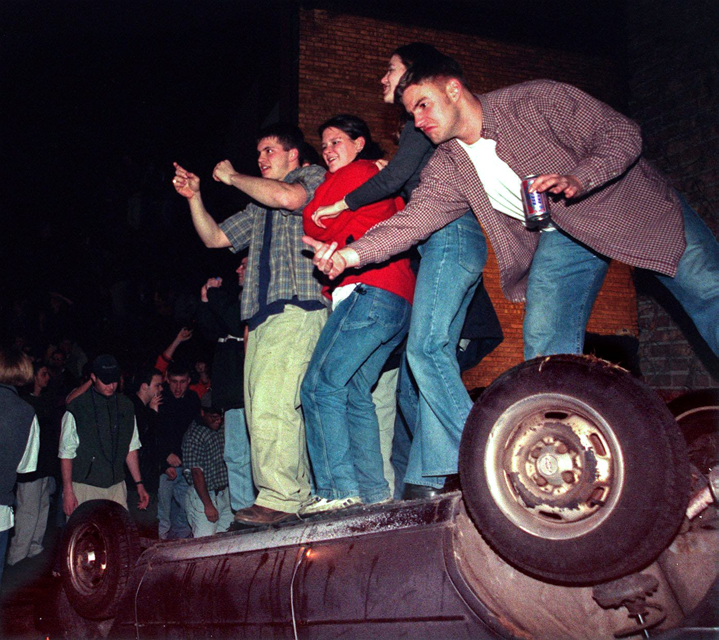 People mount on an overturned automobile in East Lansing on Saturday, Mar 27, 1999.
