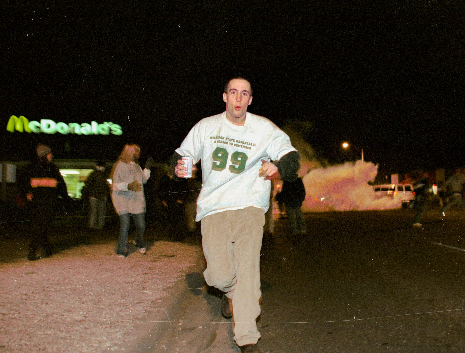 A young man runs carrying a beer after tear gas was fired into a crowd on Saturday, March 27, 1999, in East Lansing.