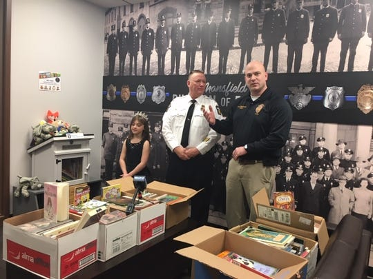 Valerie Duffey, 8, of Lexington, donated over 330 books to the Mansfield Police Department free library for kids who come to the station with adults on police business. Mansfield police Chief Ken Coontz, center, and Assistant police Chief Keith Porch thanked her for the donation to the library which honors the memory of the late Mansfield police Officer Brian Evans.