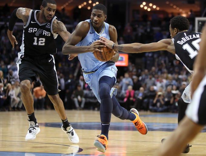 Memphis Grizzlies forward Jaren Jackson Jr. drives in between San Antonio Spurs defenders LaMarcus Aldridge, left, and DeMar DeRozan during their game at the FedExForum on Tuesday, Feb. 12, 2019.