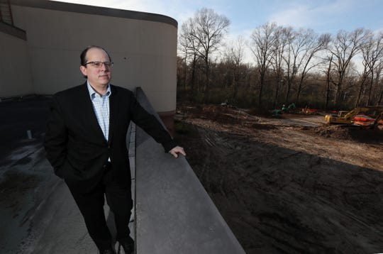 Paul Chandler, executive director of the Germantown Performing Arts Center, stands on the roof of the center, overlooking the beginning stages of construction for The Grove, GPAC's outdoor performance venue slated to be finished next year.