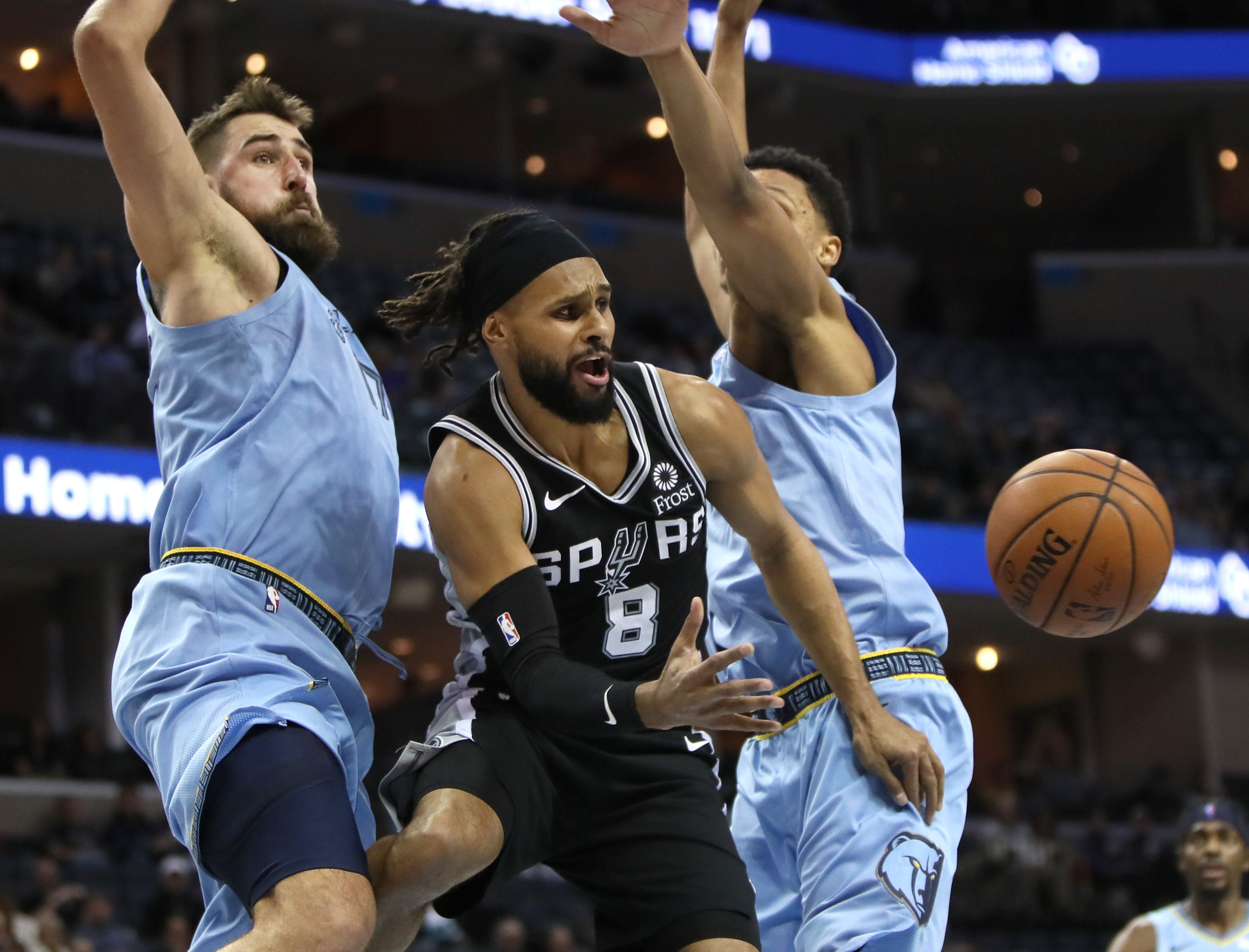 Memphis Grizzlies center Jonas Valanciunas, left, and forward Ivan Rabb defend a pass against San Antonio Spurs guard Patty Mills during their game at the FedExForum on Tuesday, Feb. 12, 2019.