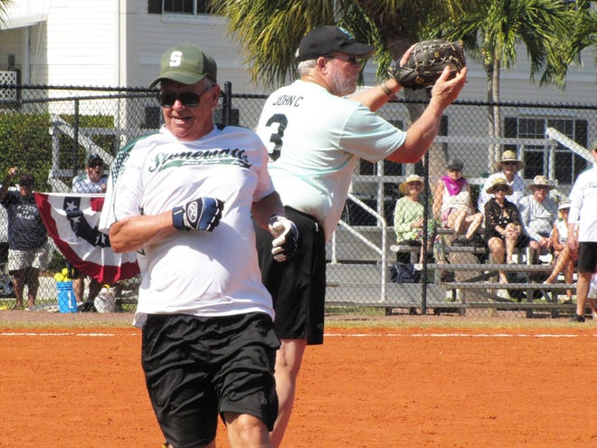 Mark Comolli legs out a base hit just before Snook Inn's John Cavanagh catches the ball at first base.