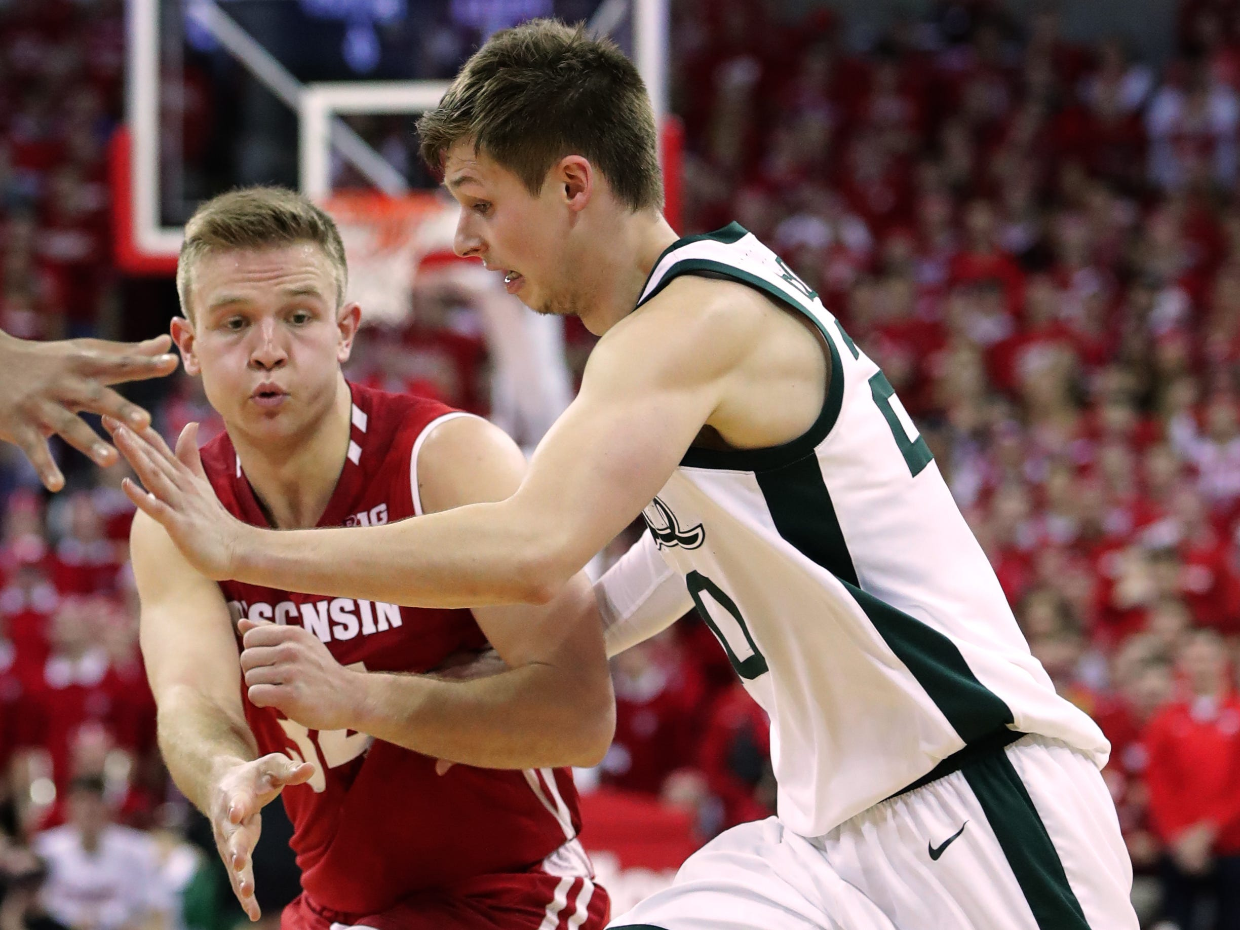 Wisconsin guard Brad Davison threads a bounce pass in front of Michigan State guard Matt McQuaid.