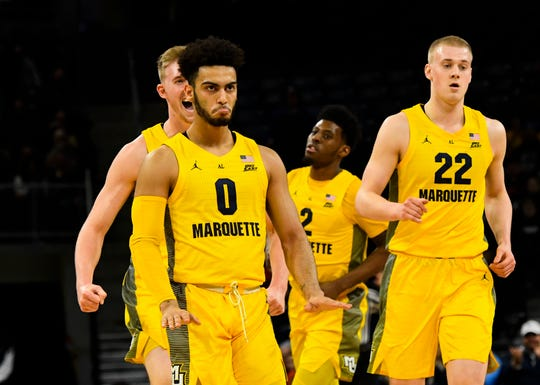 Marquette guard Markus Howard (left)  celebrates one of his three-pointers.