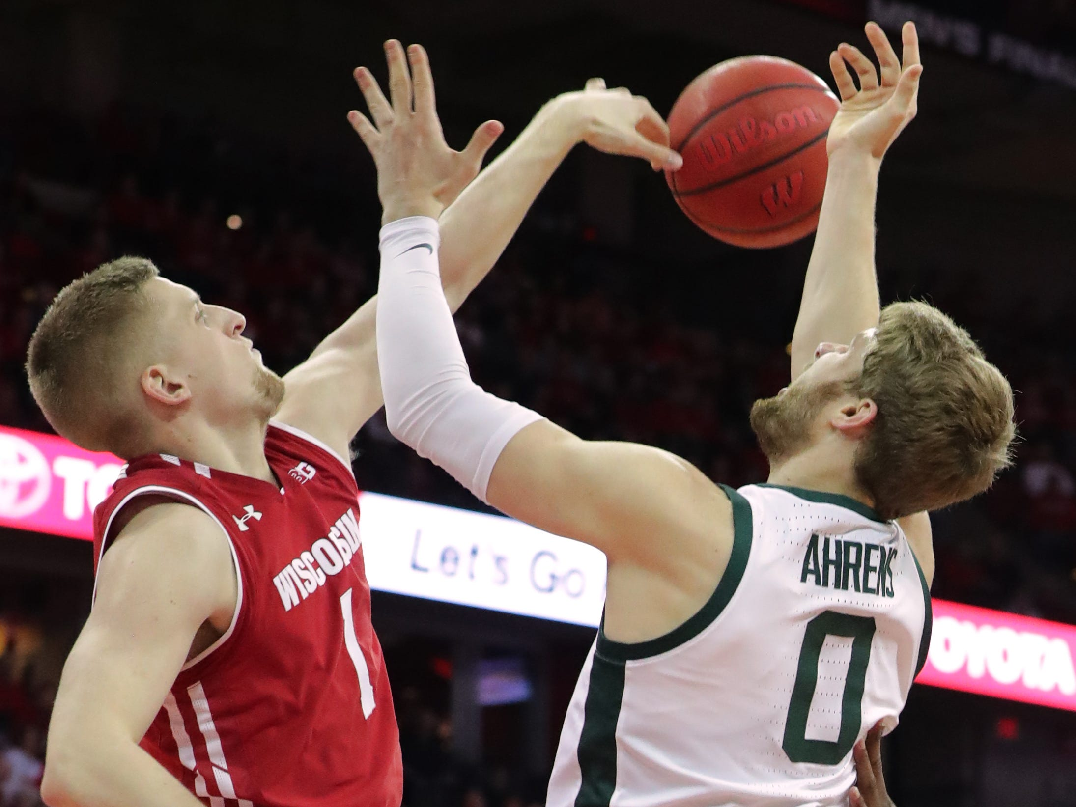 Wisconsin guard Brevin Pritzl blocks a shot by Michigan State forward Kyle Ahrens.
