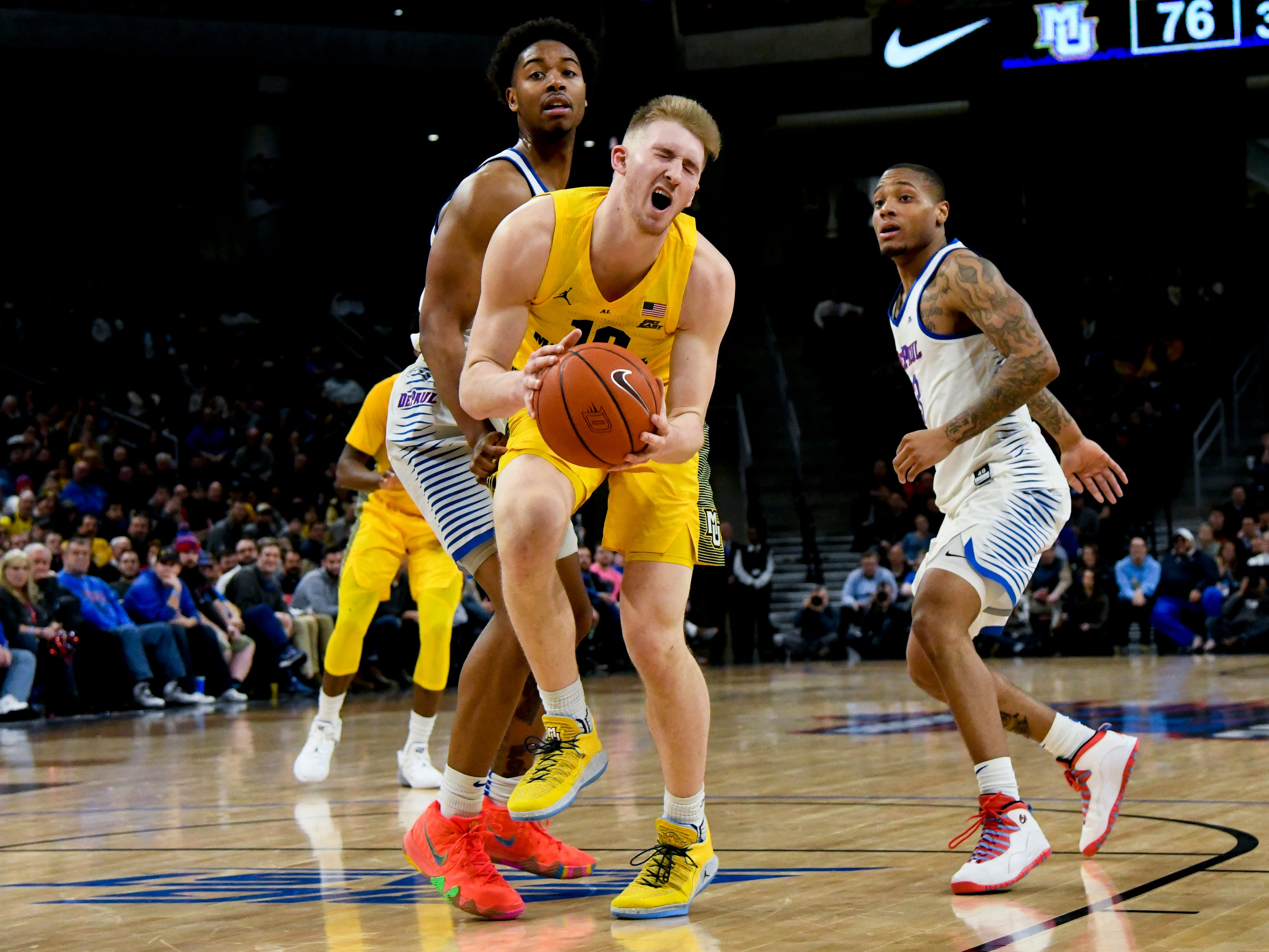 Marquette forward Sam Hauser is  poked in the eye while fighting for control of the ball with DePaul guard Eli Cain.