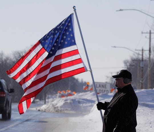 """""""I'm just supporting Officer Rittner and his family and all  law enforcement and first responders,"""" said Timothy Nelson as he holds a flag outside Oak Creek Assembly of God Church, where visitation and funeral services were being held for Milwaukee Police Officer Matthew Rittner."""