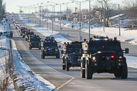 A line of police vehicles escorts the funeral procession of Milwaukee Police Officer Matthew Rittner from Oak Creek Assembly of God Church to Krause Funeral Home in Brookfield. They are shown heading east along East Rawson Avenue in Oak Creek.