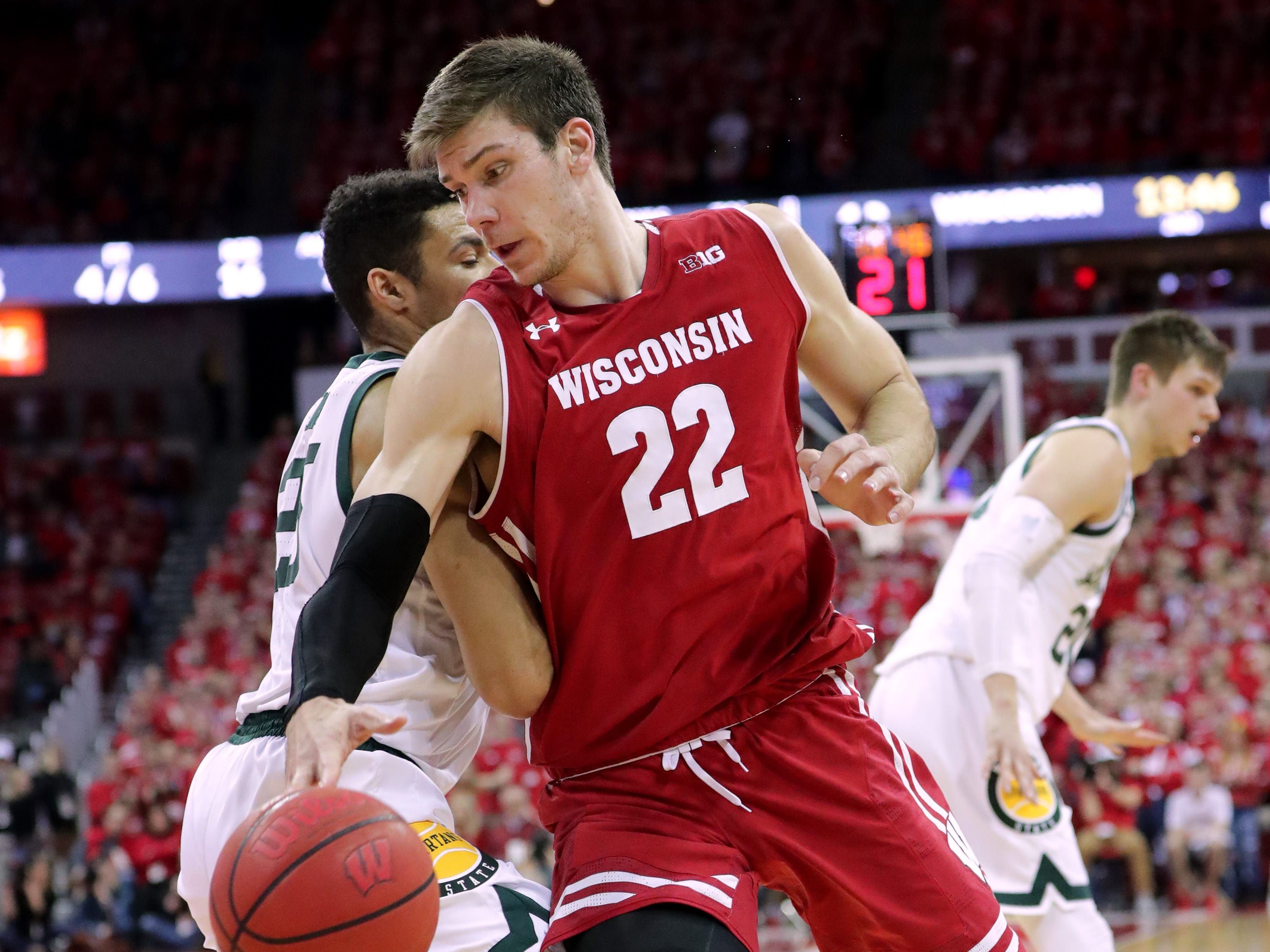 Michigan State forward Kenny Goins fouls Wisconsin forward Ethan Happ on his way to the basket.