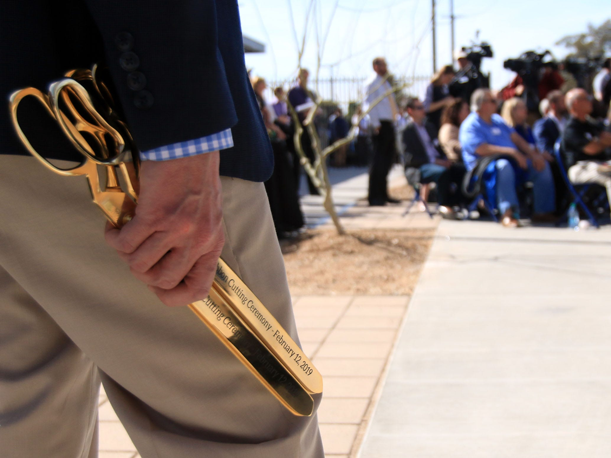 Tyler Barnes holds scissors that are used in the  a ribbon-cutting ceremony to unveil the new Milwaukee Brewers spring training facility.