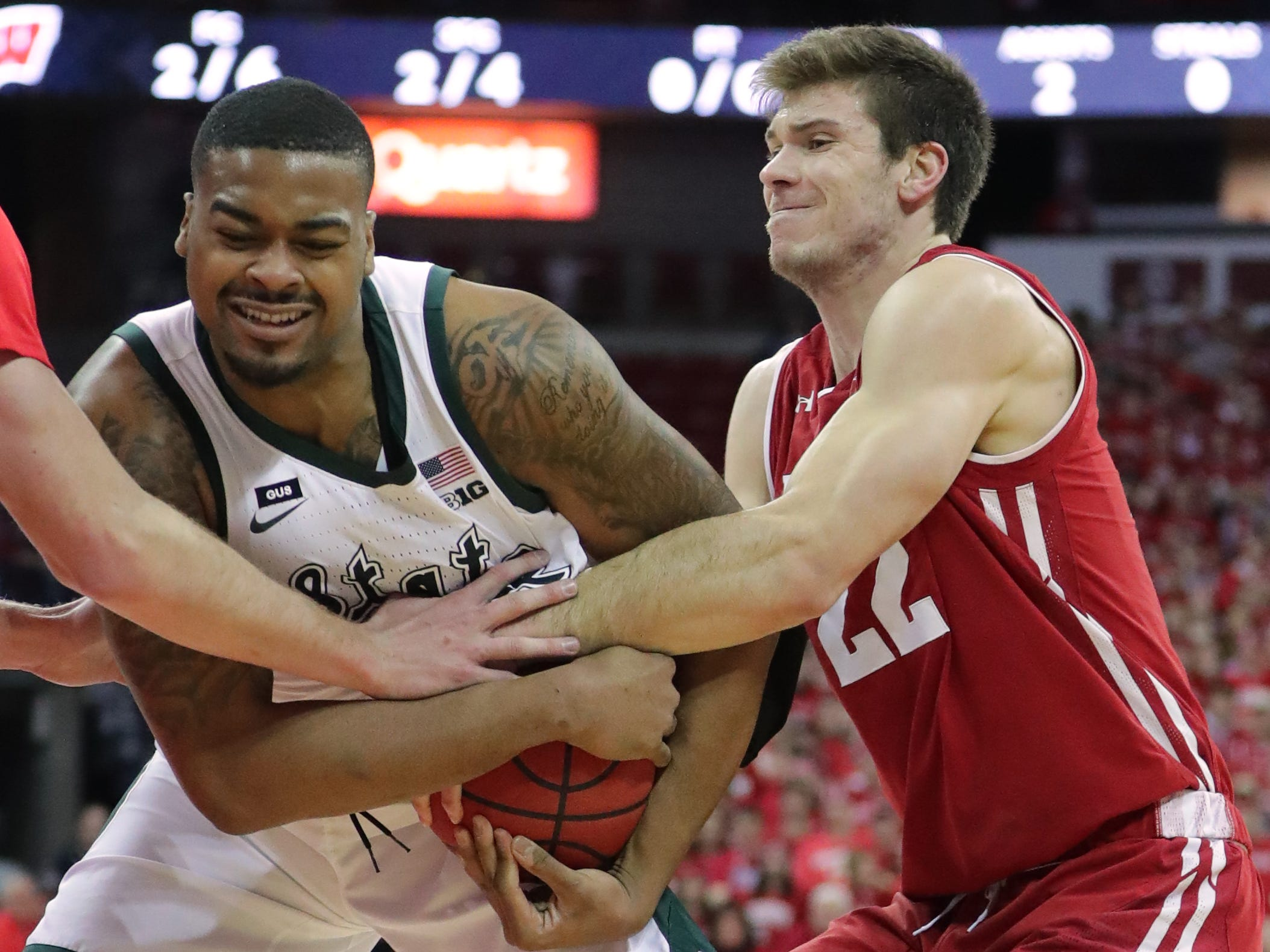 Wisconsin forward Ethan Happ tries to wrestle the ball from Michigan State forward Nick Ward on Tuesday night.