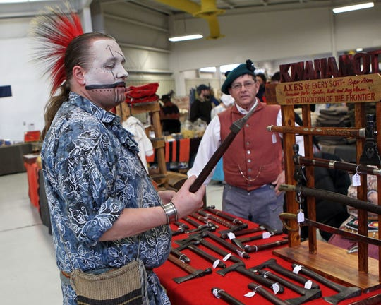 Daniel Youngbauer of Oshkosh, dressed in traditional Meskwaki Indian face paint, checks out the tomahawks at the Echoes of the Past historical trade fair in 2018.