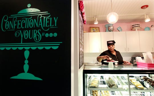 Confectionately Yours owner Adija Greer-Smith arranges Marley Bites (turtle candies meet pretzels) at her shop at Sherman Phoenix. Oversize cookies are another specialty of the shop; one called the Phoenix adds pecans to a chocolate chip-oatmeal cookie base.