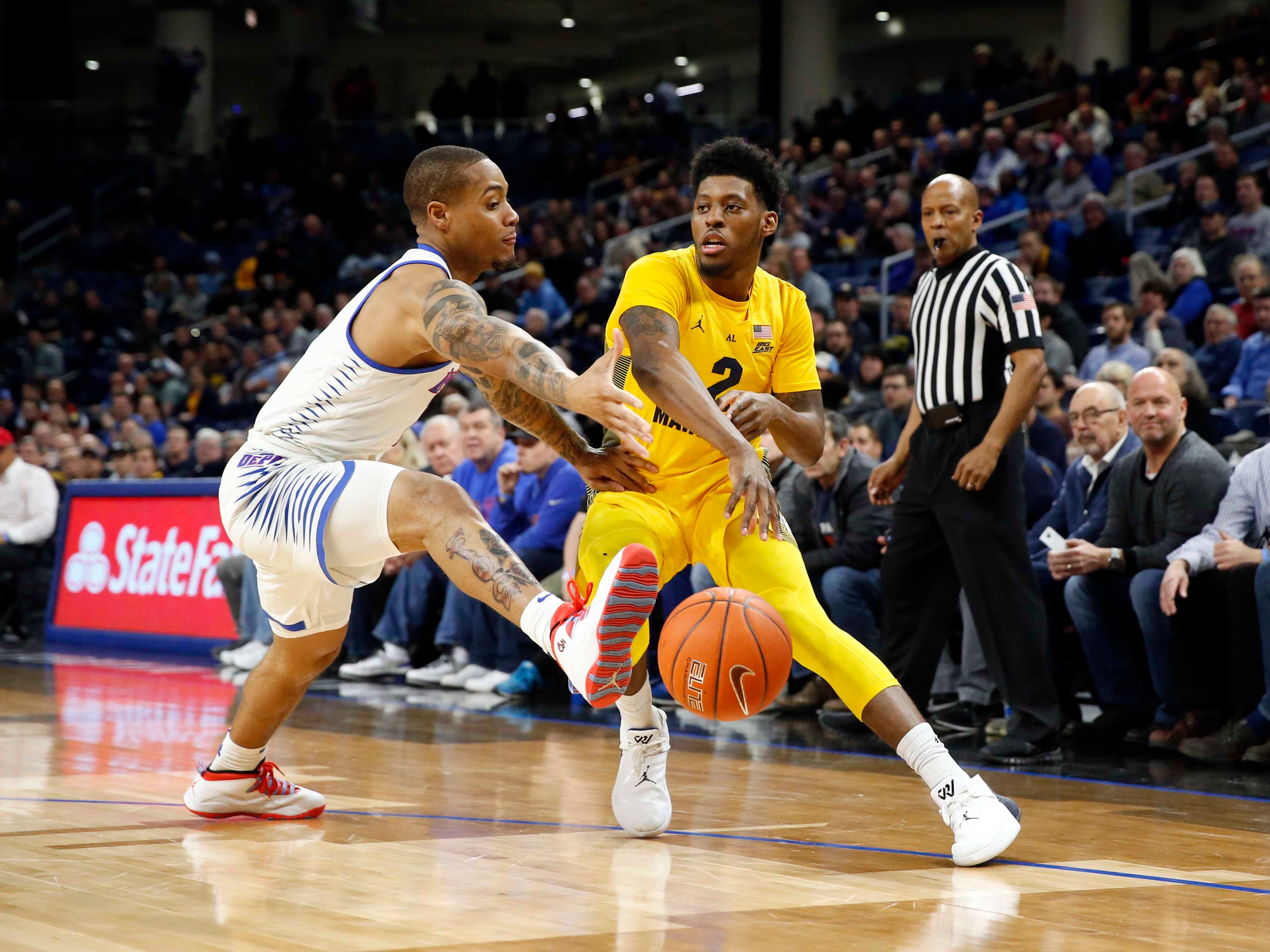 Marquette forward Sacar Anim finds room to pass around DePaul guard Devin Gage.