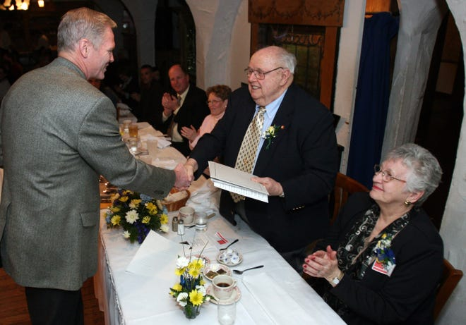 Former Thiensville Fire Chief William Rausch (center) receives a commendation from Janesville Fire Chief Larry Grorud, the former president of the International Association of Fire Chiefs, during Rausch's retirement dinner on Jan. 19, 2008. Also pictured is Rausch's wife, Pat, who volunteered with the fire department for 25 years.