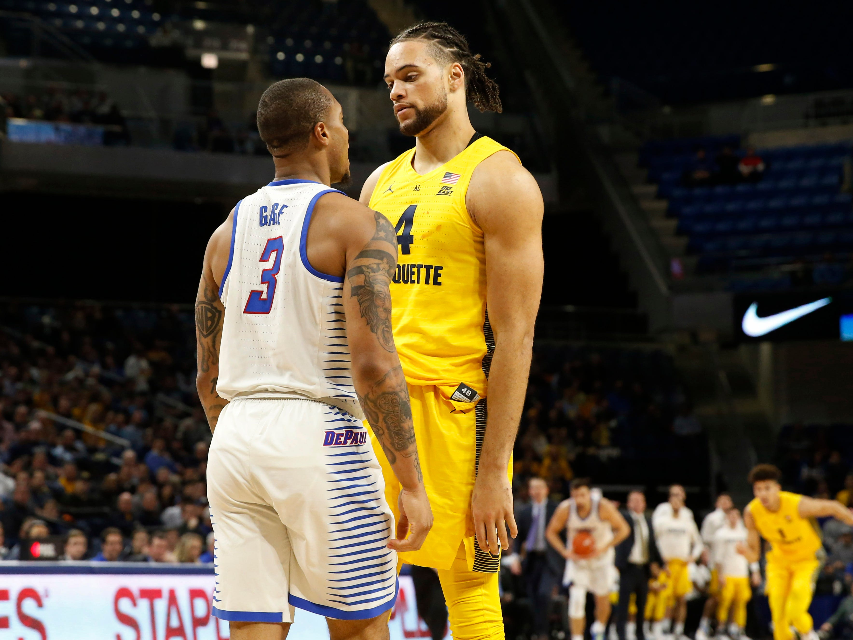 DePaul guard guard Devin Gage  and Marquette Golden Eagles forward Theo John exchange words during the first half.