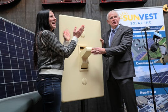 Leslie Montemurro (left), co-owner of Fuel Cafe, and Milwaukee Mayor Tom Barrett flip the ceremonial switch Wednesday to celebrate Fuel Cafe's solar power system. Fuel Cafe estimates the solar panels will save the restaurant up to $6,000 per year and offset 7.5 percent of its energy use.